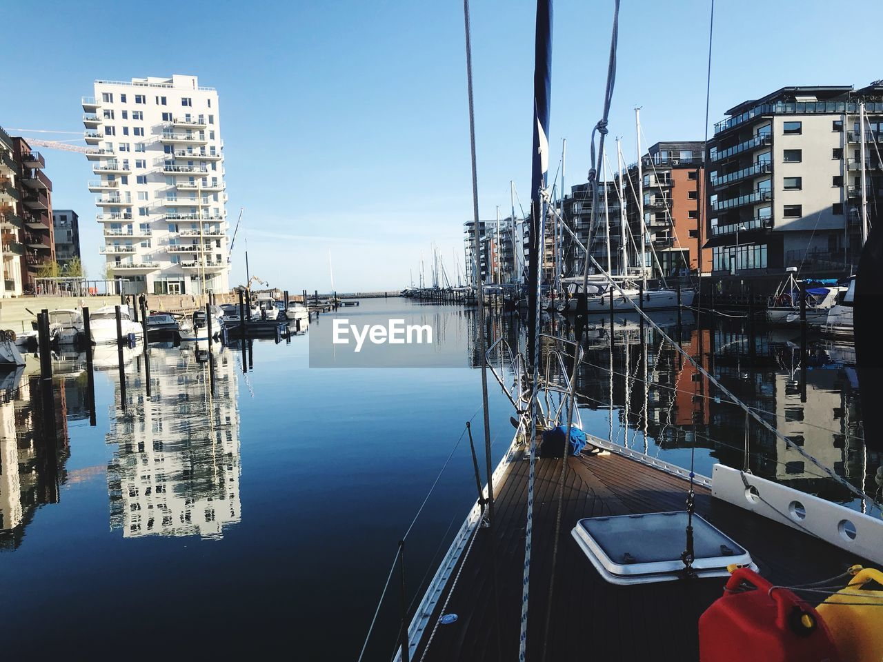 Sailboats Moored At Harbor Against Buildings In City