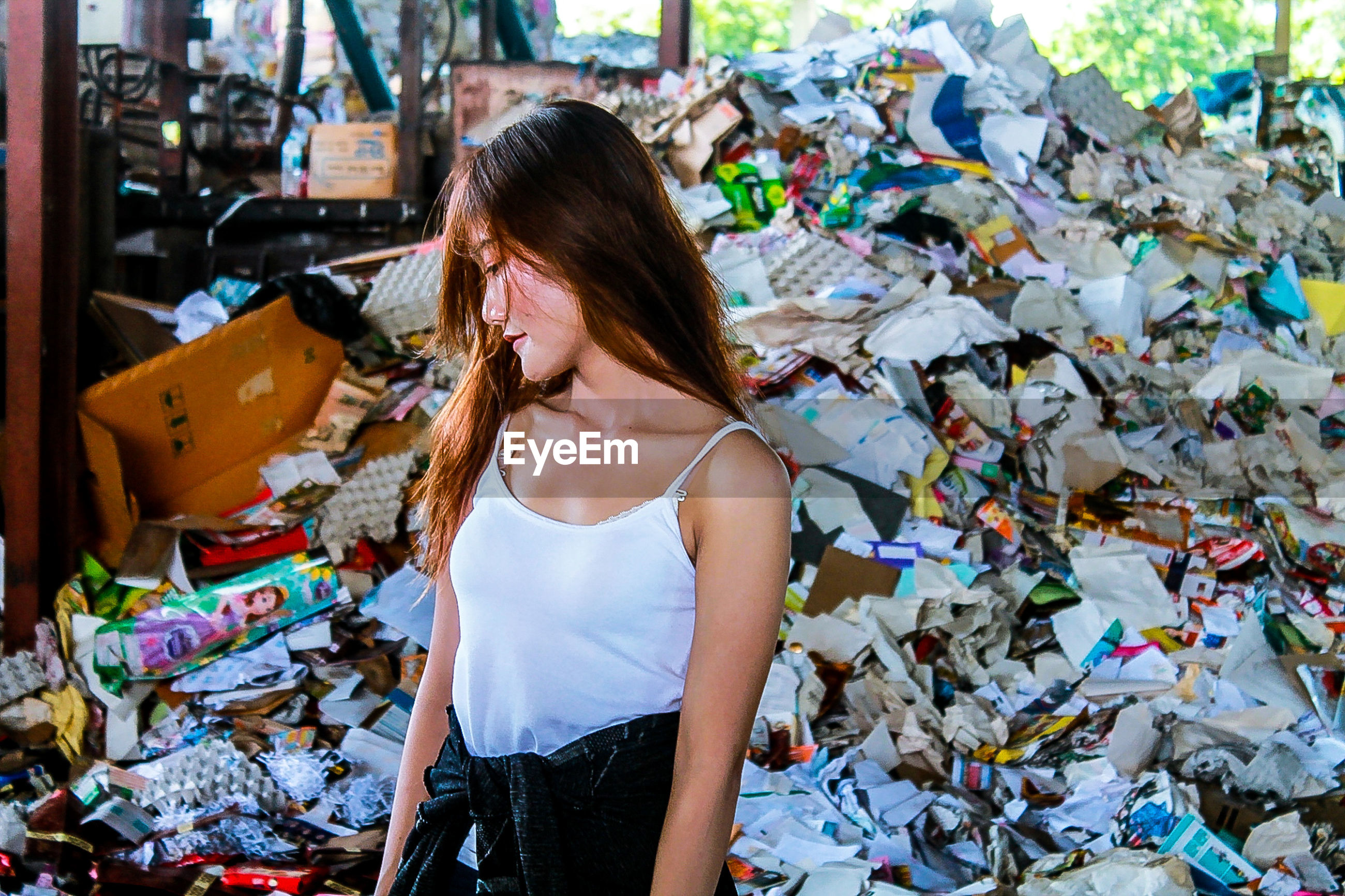 Young woman standing against garbage