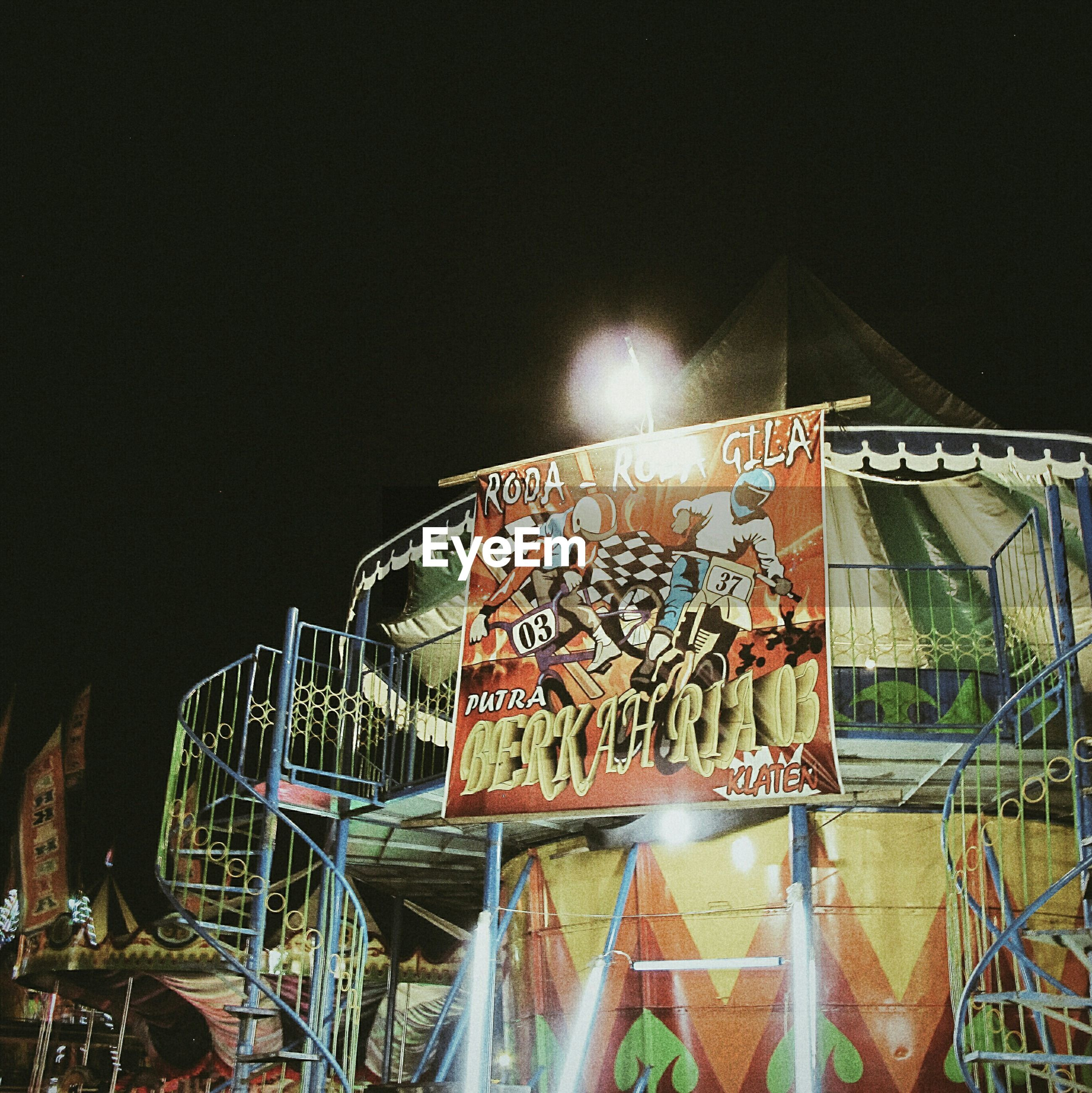 built structure, graffiti, architecture, building exterior, night, bicycle, arts culture and entertainment, outdoors, men, clear sky, art, text, metal, wall - building feature, creativity, illuminated, city, amusement park, low angle view