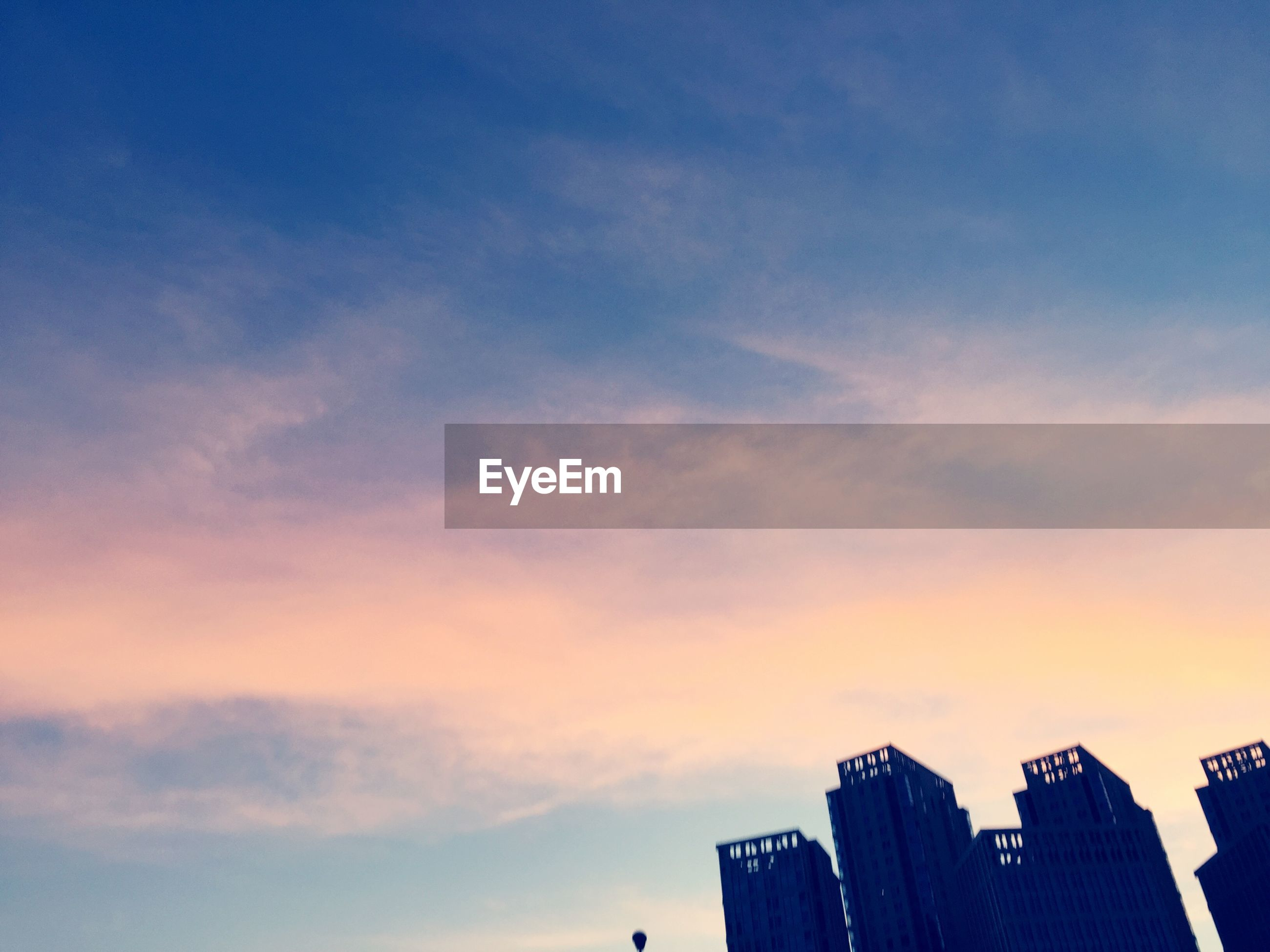 building exterior, architecture, built structure, sunset, low angle view, sky, city, skyscraper, orange color, cloud - sky, building, tall - high, modern, office building, cloud, outdoors, tower, no people, residential building, high section