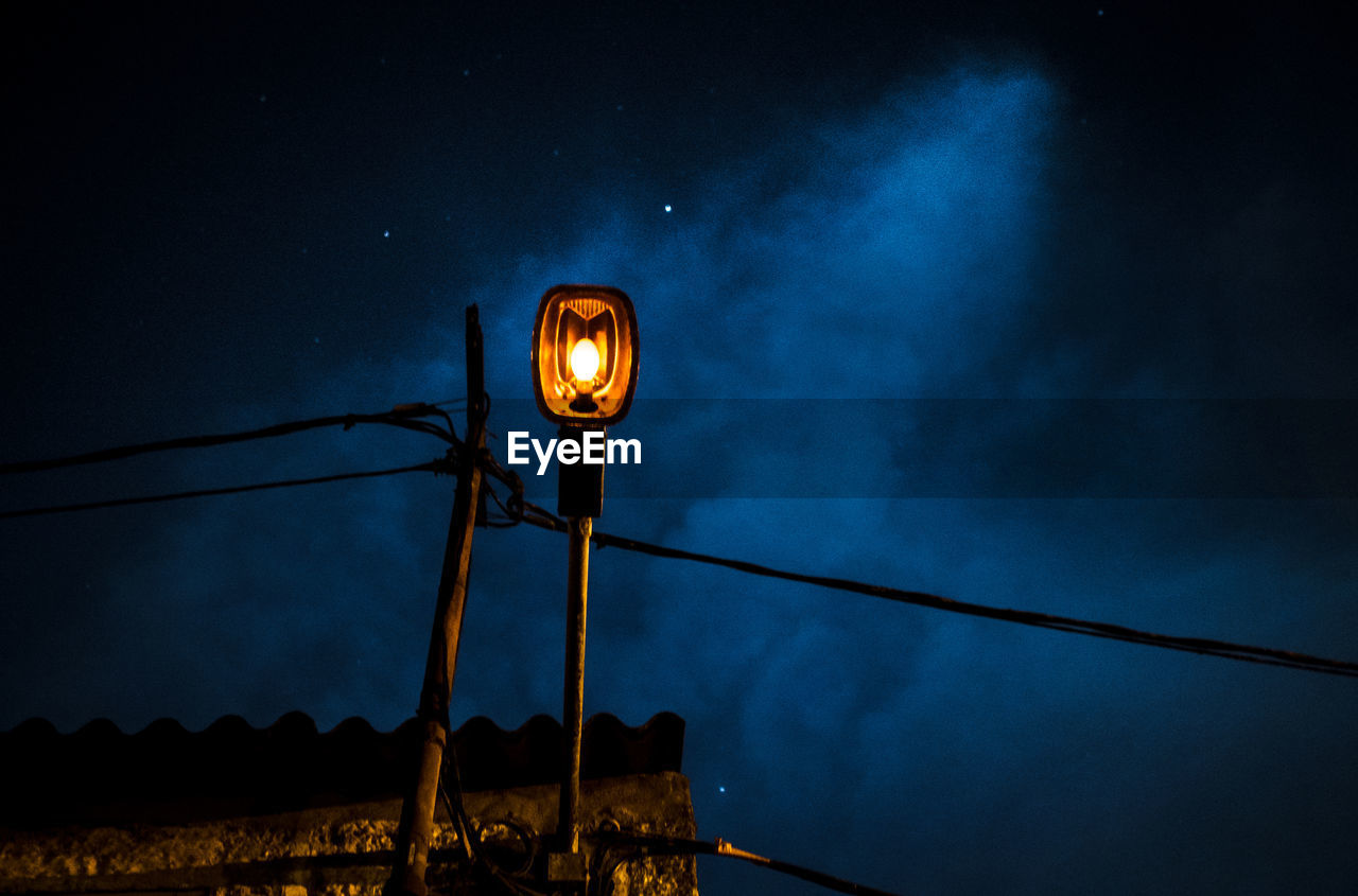Low angle view of street light pole at night