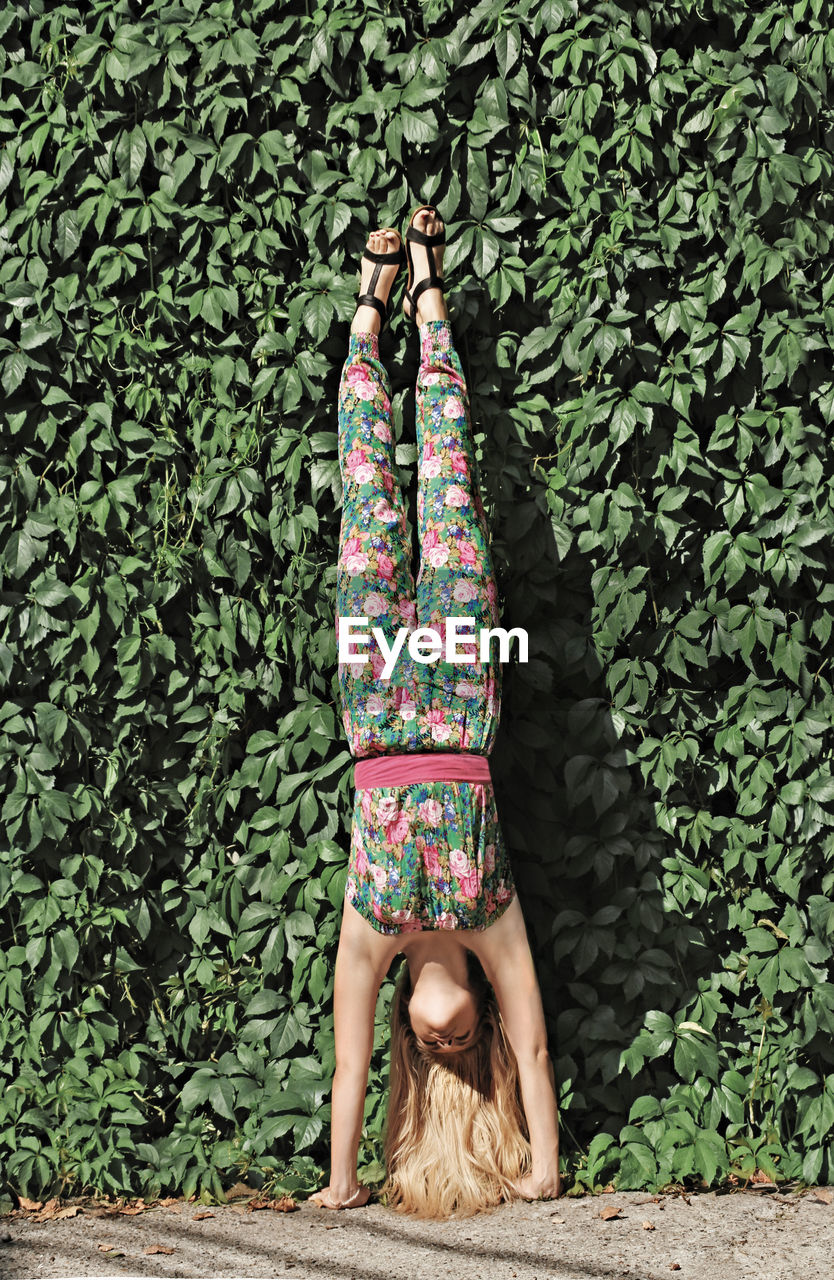 Young Women Practicing Handstand Against Plants