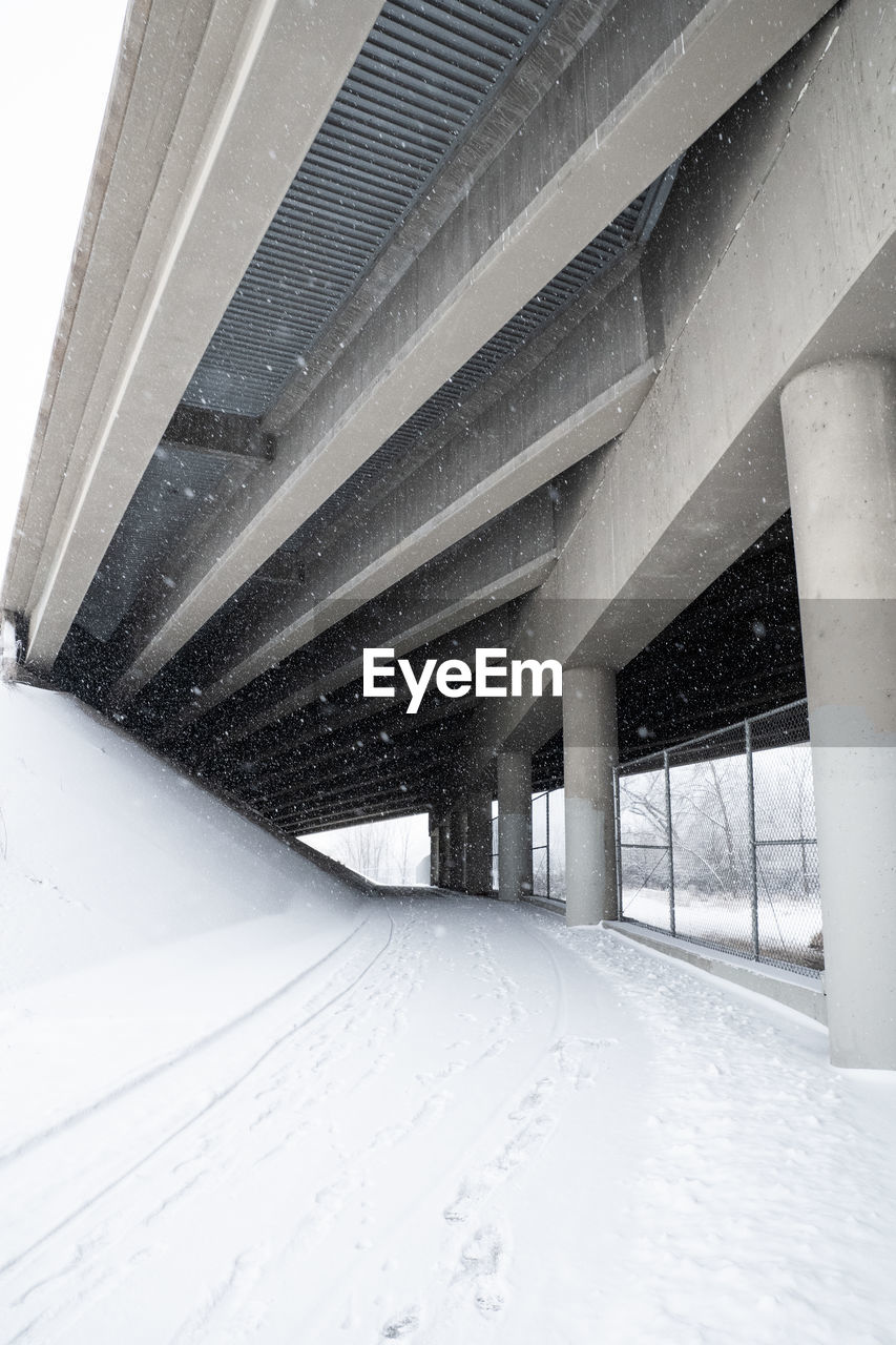architecture, winter, cold temperature, built structure, snow, architectural column, transportation, connection, bridge, no people, bridge - man made structure, road, the way forward, day, nature, direction, covering, white color, city, snowing, outdoors, ceiling, long