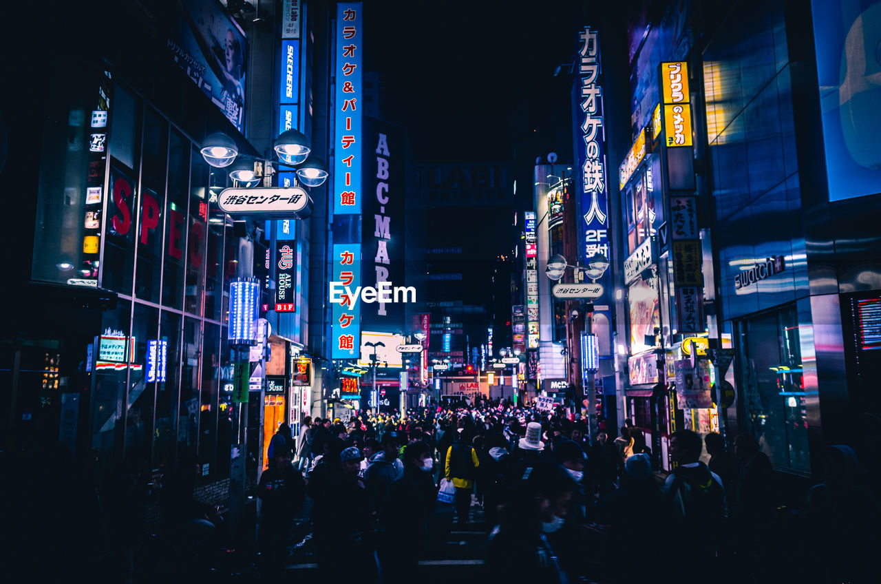 illuminated, architecture, city, building exterior, night, built structure, group of people, large group of people, real people, crowd, city life, advertisement, text, communication, building, street, lifestyles, men, commercial sign, sign, neon, outdoors, office building exterior, skyscraper, nightlife