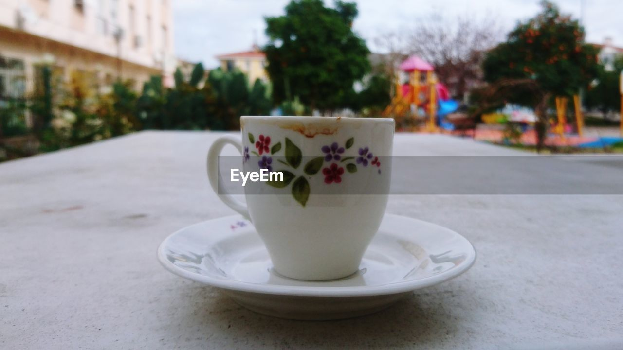 cup, mug, crockery, drink, saucer, refreshment, coffee cup, food and drink, focus on foreground, coffee, close-up, coffee - drink, table, hot drink, architecture, no people, freshness, day, still life, city, tea cup, floral pattern, non-alcoholic beverage