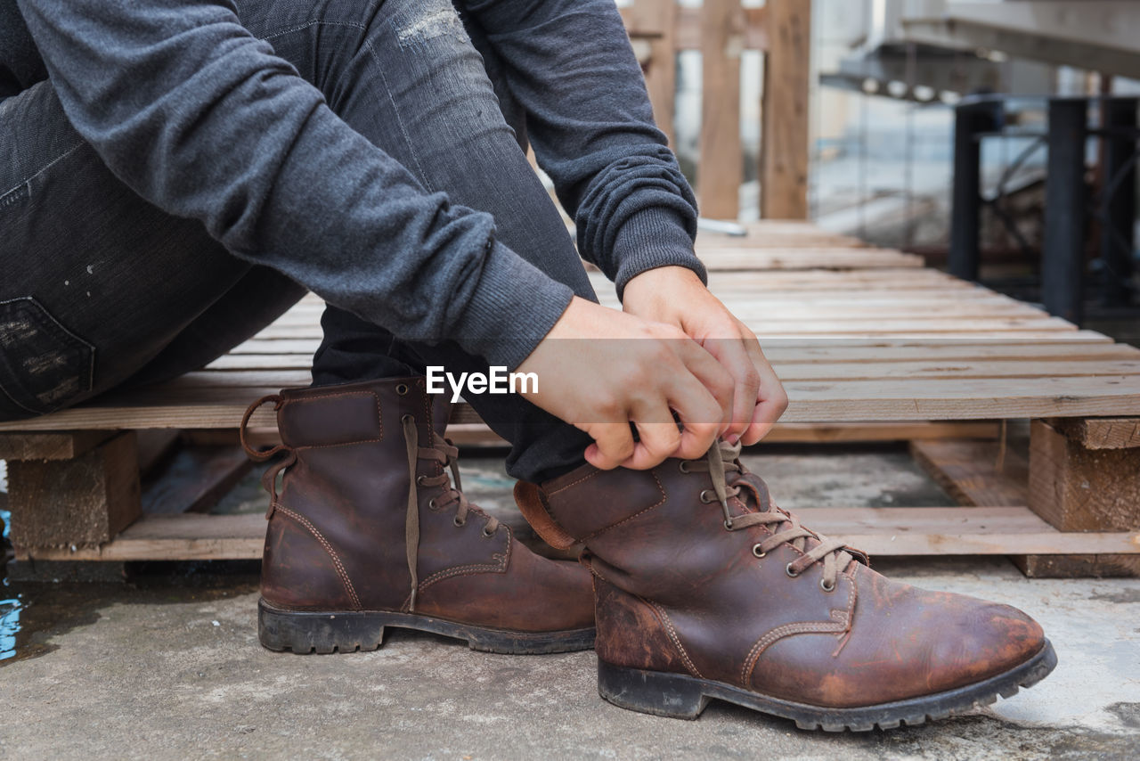 Low section of man tying shoelace while sitting on palette