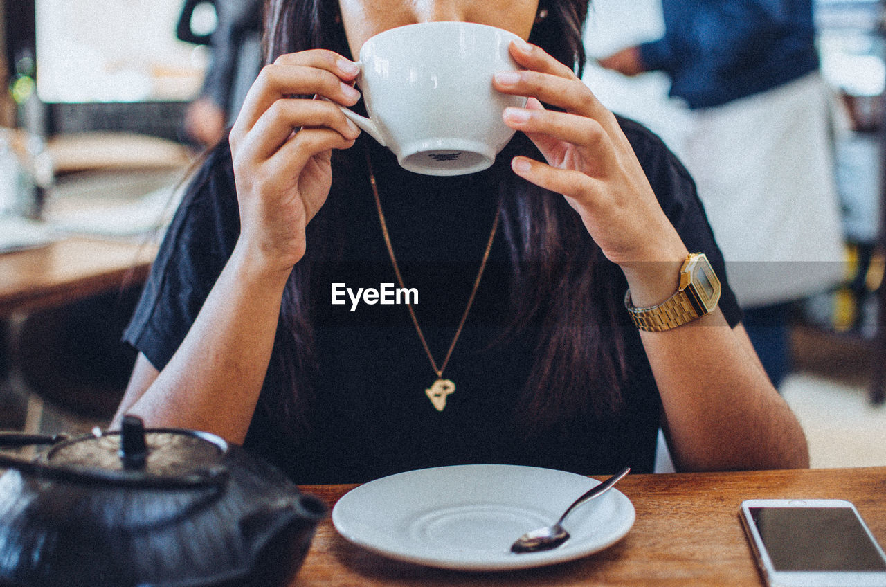 Midsection Of Woman Drinking Coffee At Table In Cafe