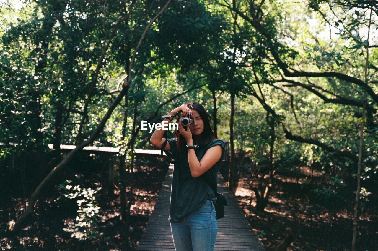 Full Length Of Woman Taking Photo By Tree Against Sky