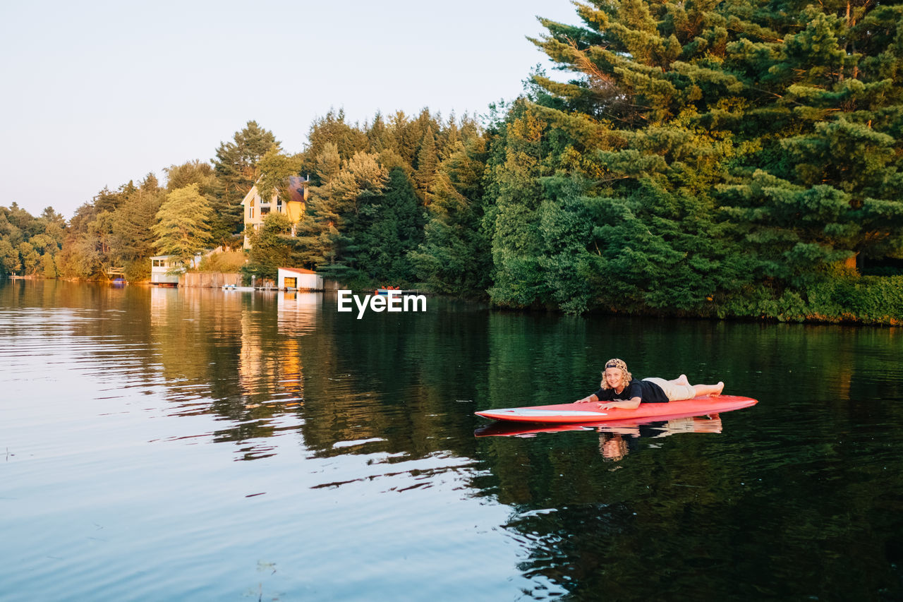 water, tree, lake, leisure activity, real people, one person, reflection, nature, day, full length, casual clothing, sitting, waterfront, lifestyles, beauty in nature, tranquility, outdoors, smiling, looking at camera, vacations, relaxation, childhood, young adult, young women, happiness, swimming, portrait, blond hair, sky, people