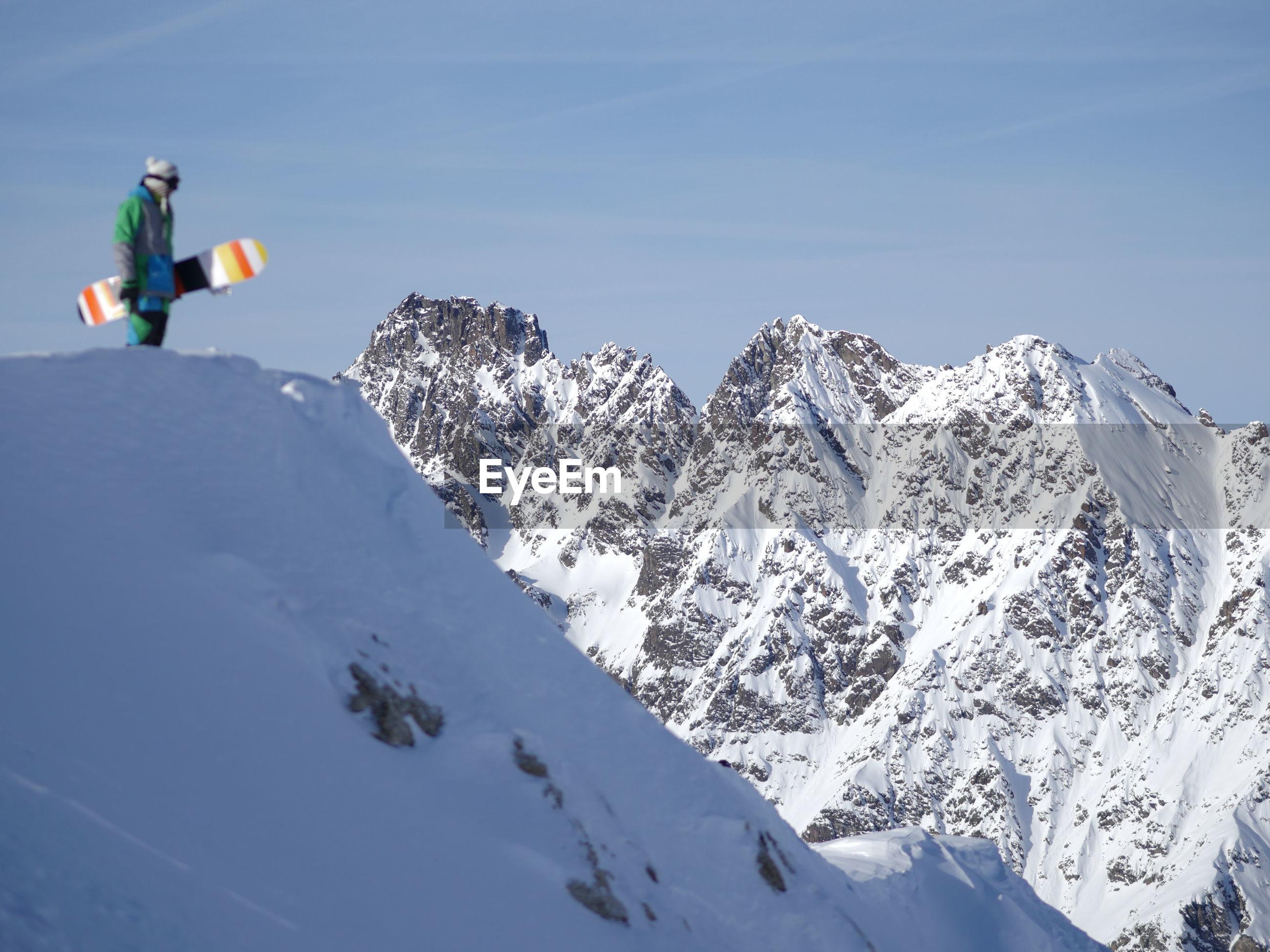Man holding snowboard on landscape