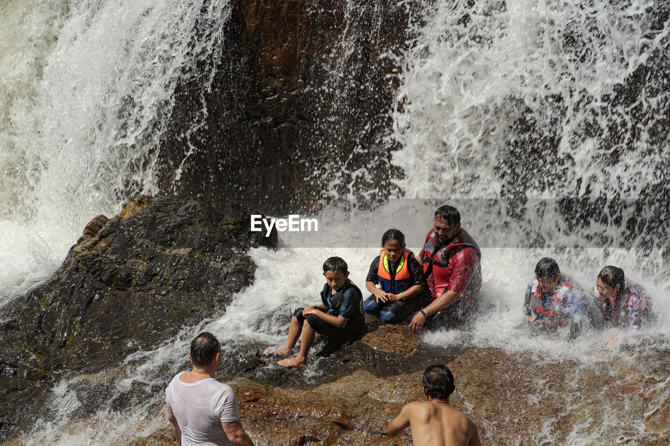 GROUP OF PEOPLE ENJOYING AT WATER