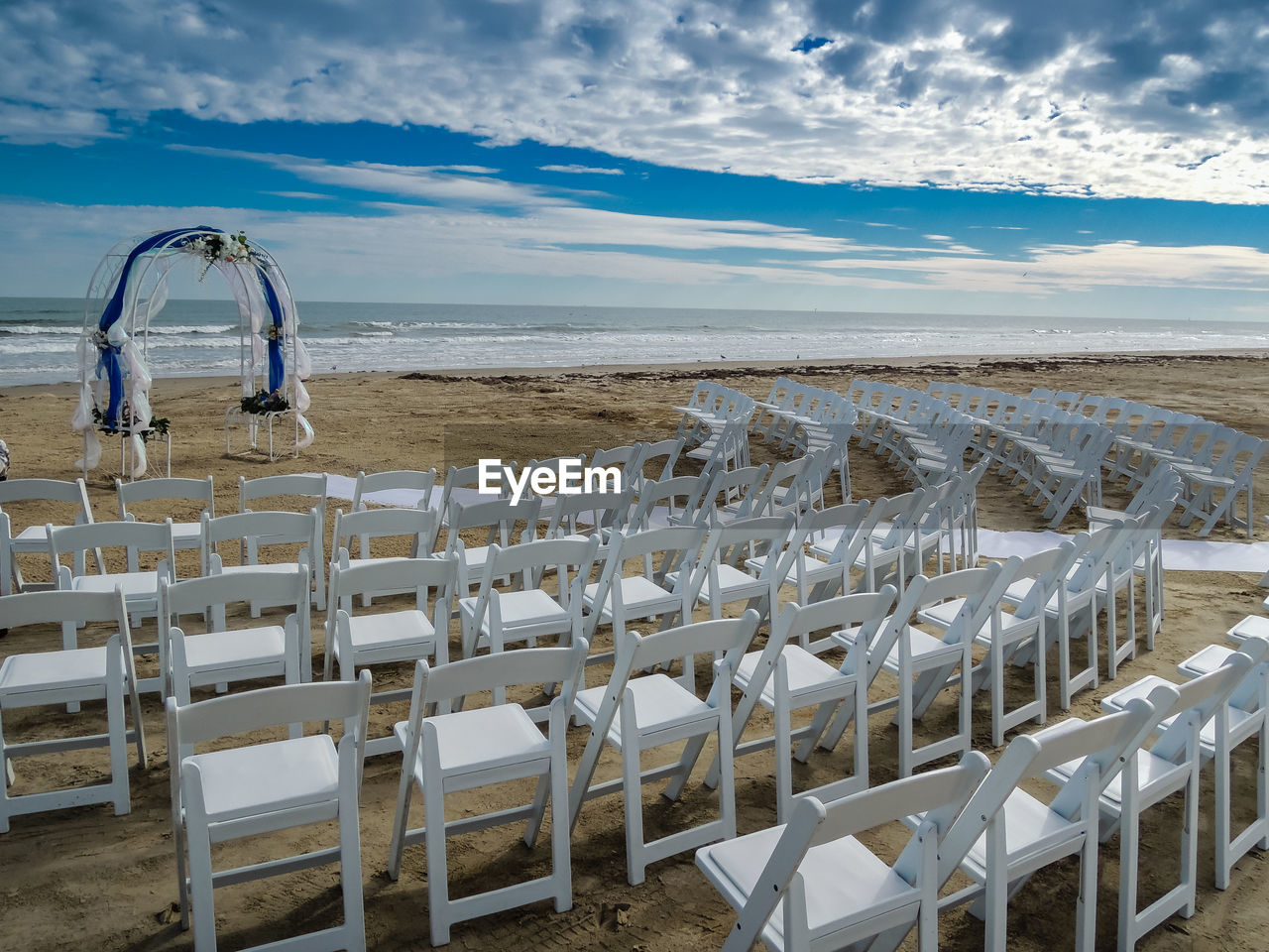 Chairs Arranged At Beach Against Cloudy Sky
