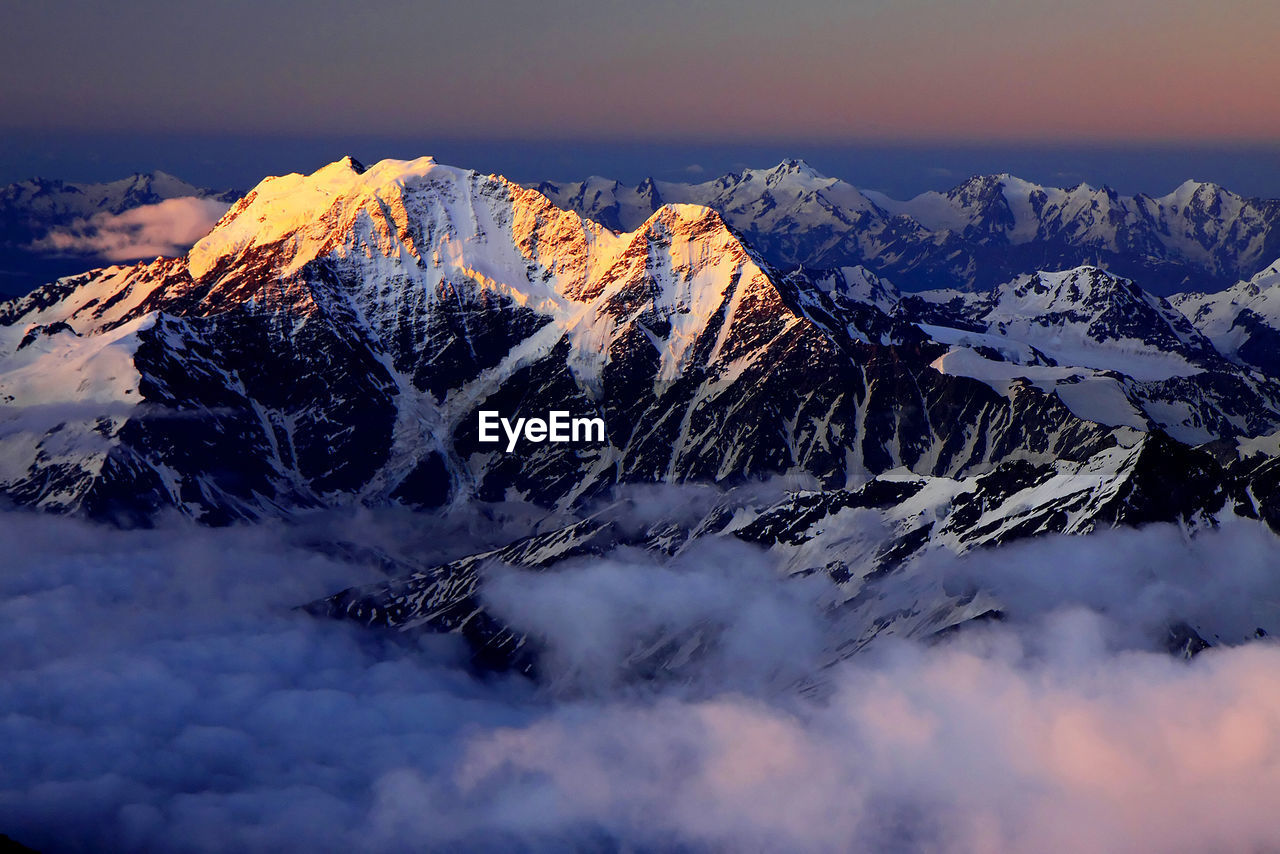 Scenic View Of Snowcapped Mountains Covered With Cloudscape At Sunset