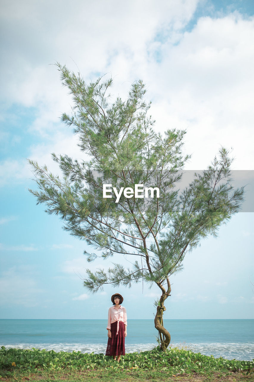 Woman standing by tree at beach against sky