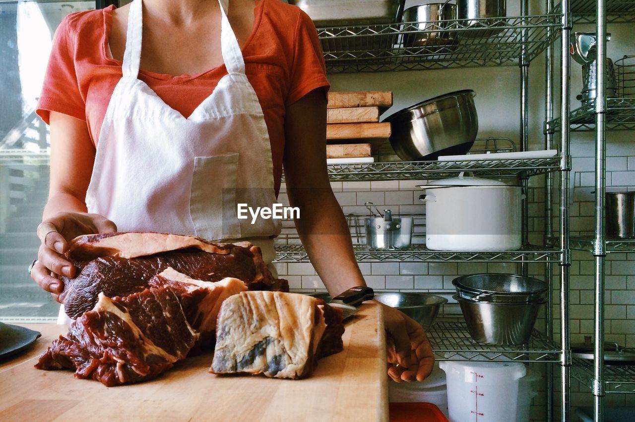 Woman Preparing Meet In Kitchen