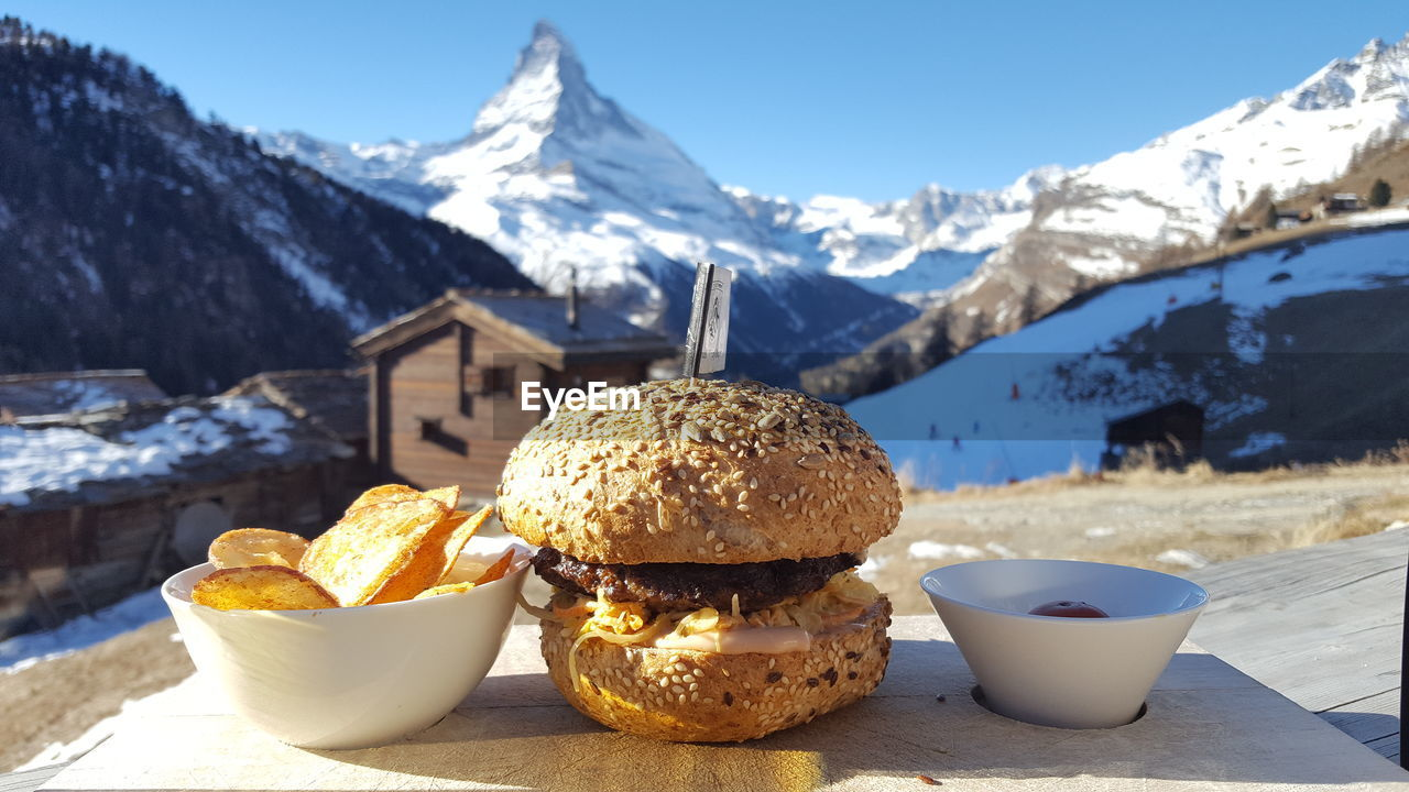 Close-Up Of Food Served On Table Against Mountains