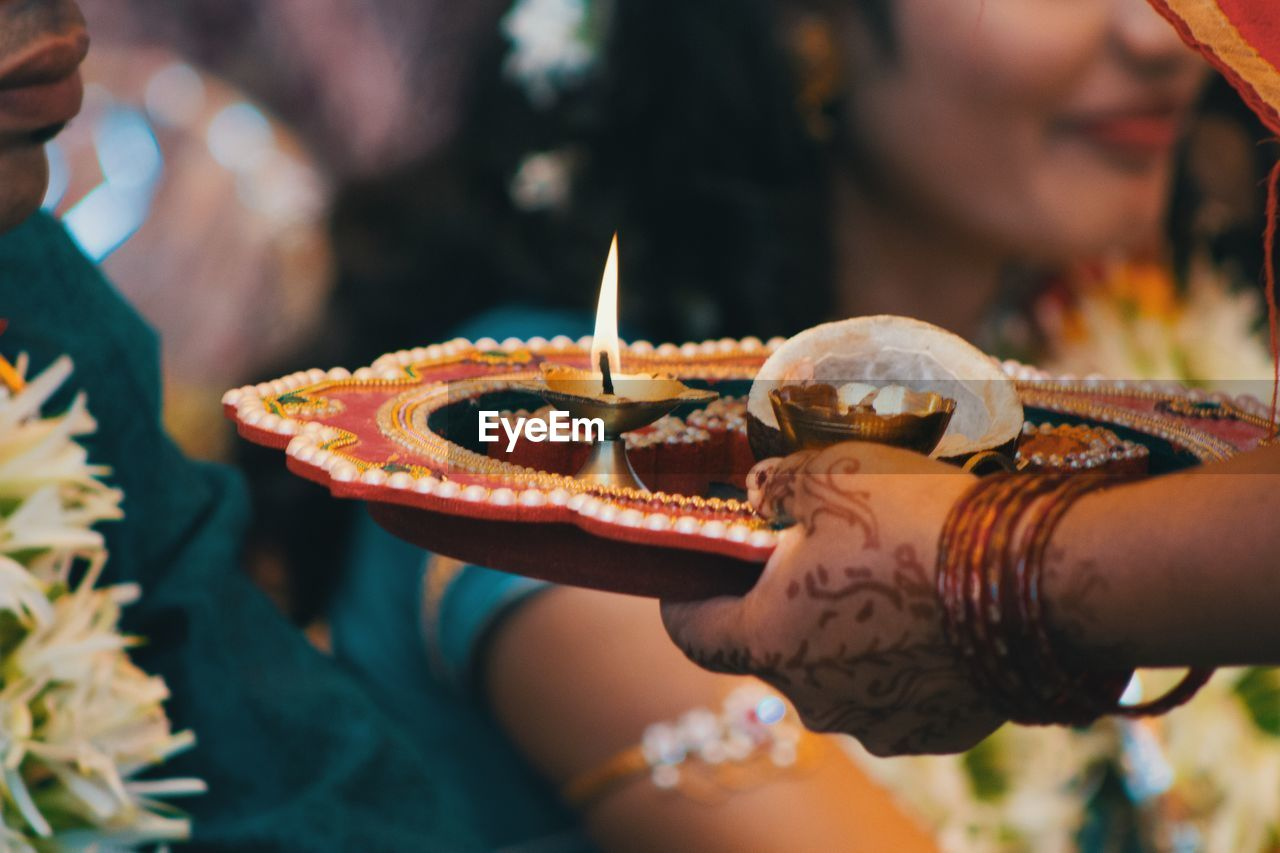Cropped Hand Of Woman Holding Diya In Plate