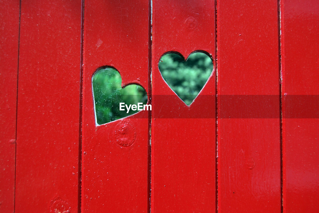 Close-up of heart shape on red fence