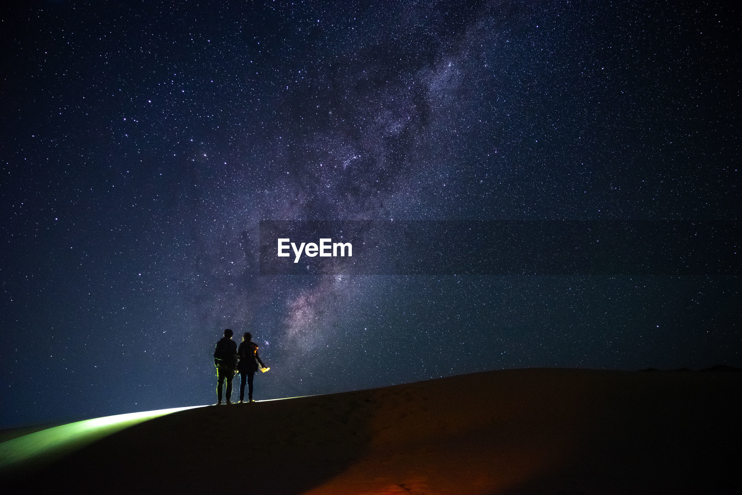 Silhouette couple standing on field against star field at night