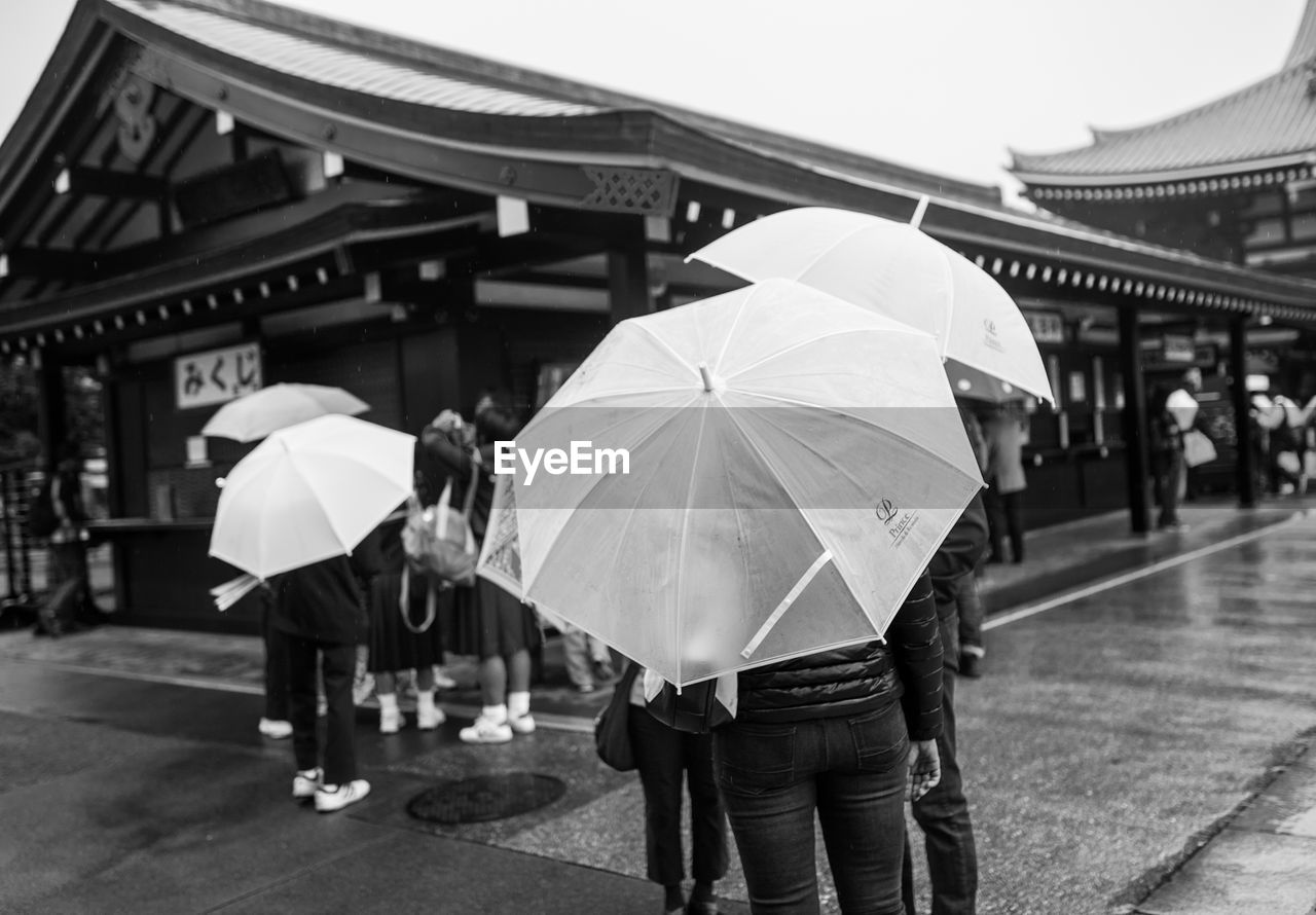 Rear view of people holding umbrella white standing against traditional building