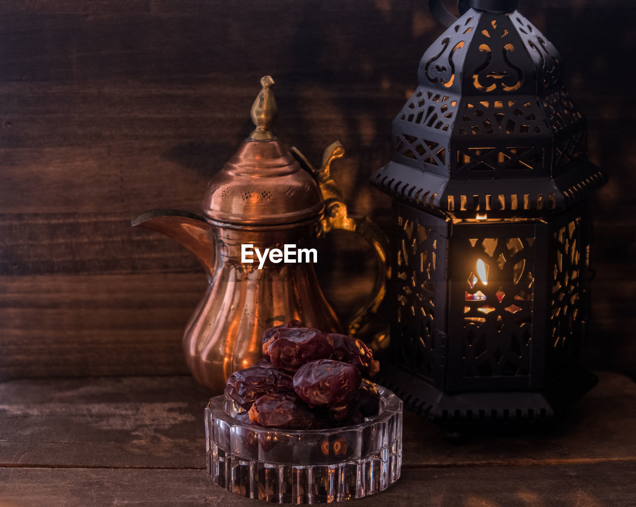 Close-up of antique teapot and lantern with raisins on table