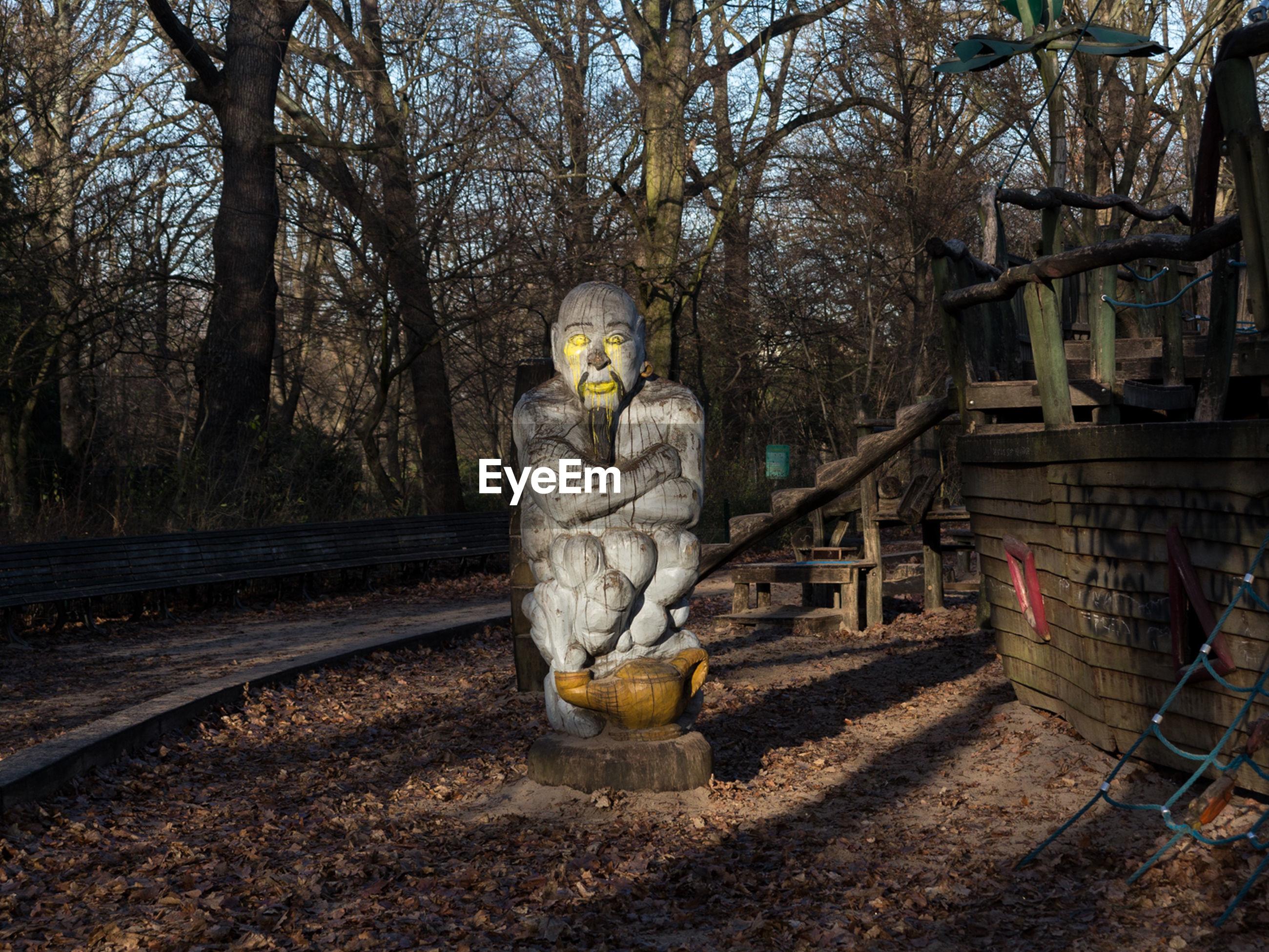Wooden male sculpture against trees at volkspark hasenheide