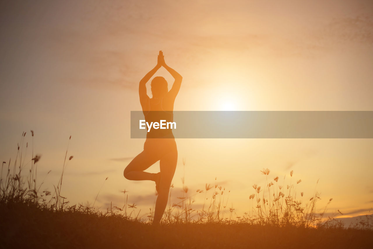 one person, sunset, lifestyles, human arm, sky, leisure activity, arms raised, real people, wellbeing, sunlight, full length, beauty in nature, field, nature, sun, exercising, healthy lifestyle, relaxation exercise, silhouette, women, outdoors, hand, lens flare, bright