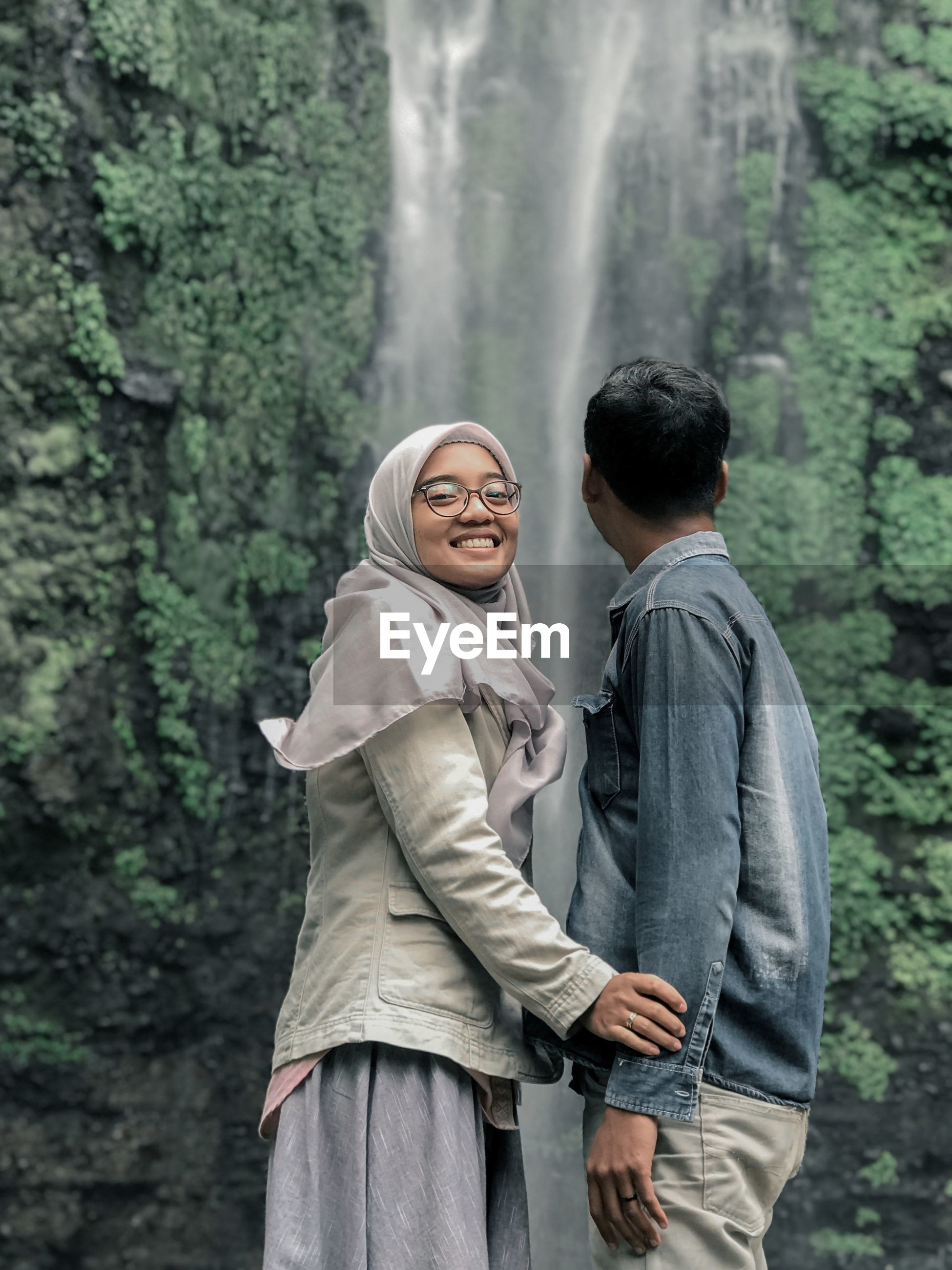 Smiling woman standing with man against waterfall