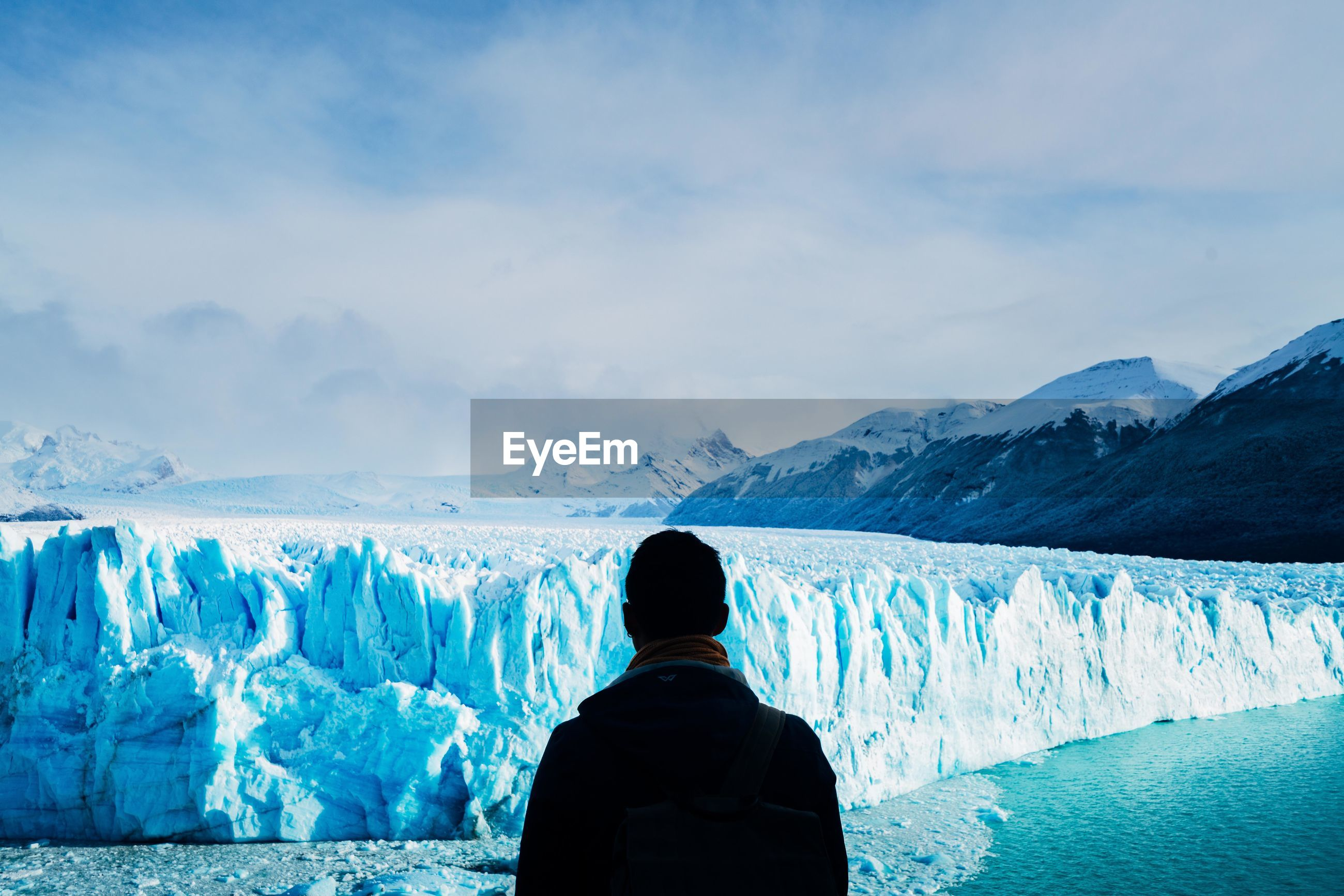 Rear view of man looking at glacier from observation point