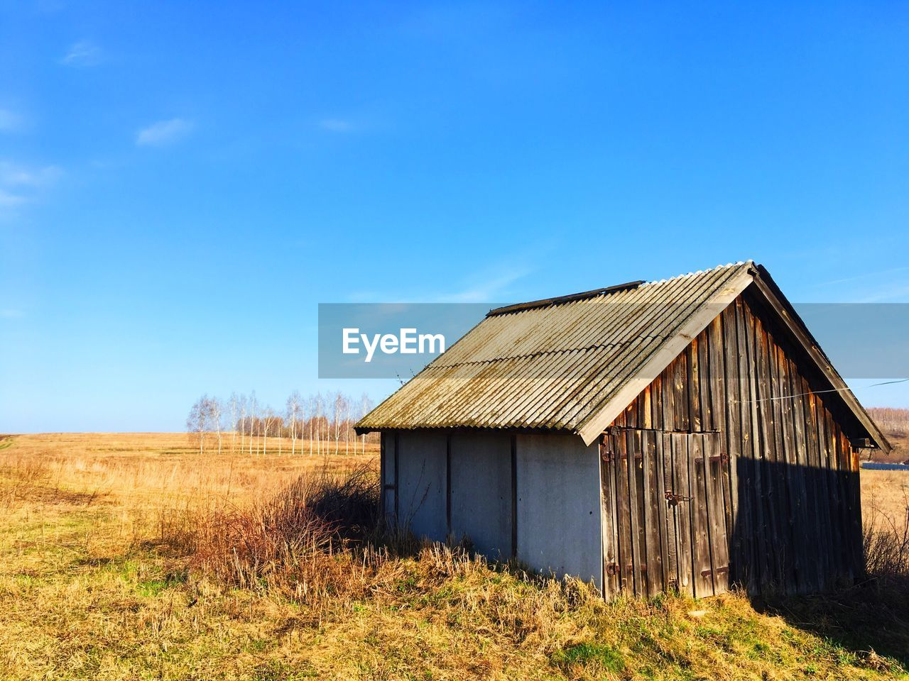 built structure, architecture, sky, field, blue, land, building exterior, nature, landscape, plant, wood - material, grass, day, building, no people, agricultural building, barn, environment, house, sunlight, outdoors