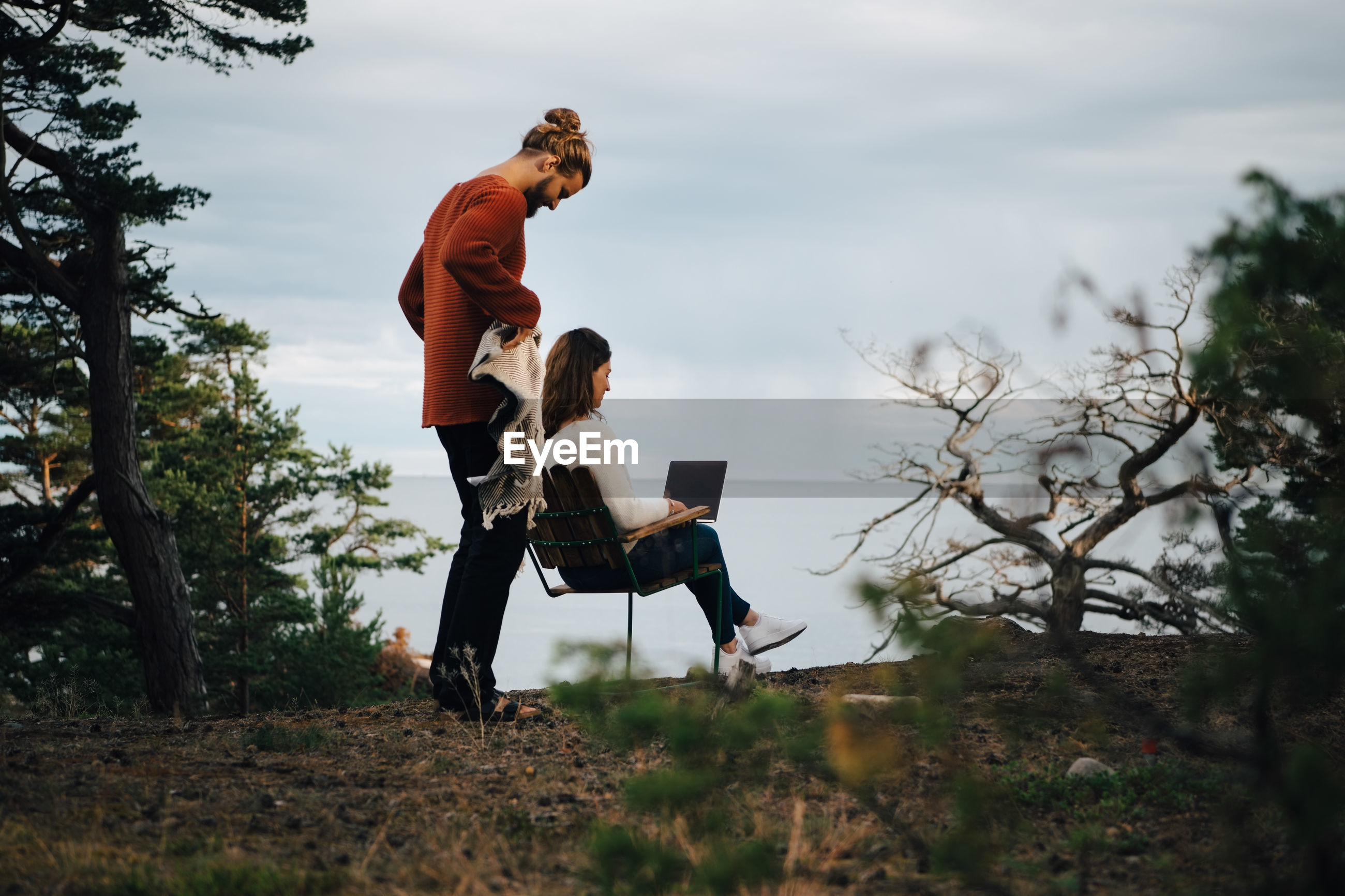SIDE VIEW OF COUPLE SITTING ON LAND