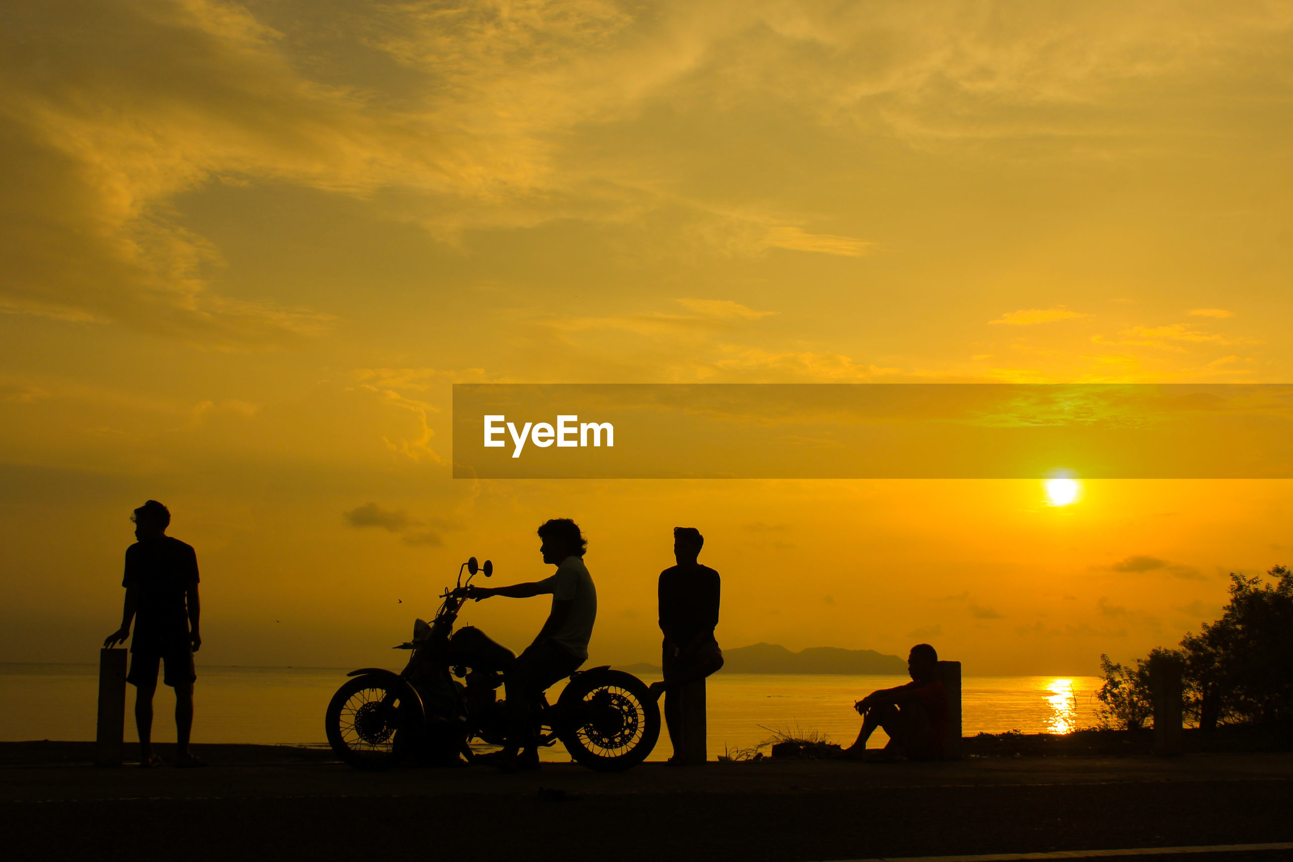 Silhouette people riding bicycle against sky during sunset