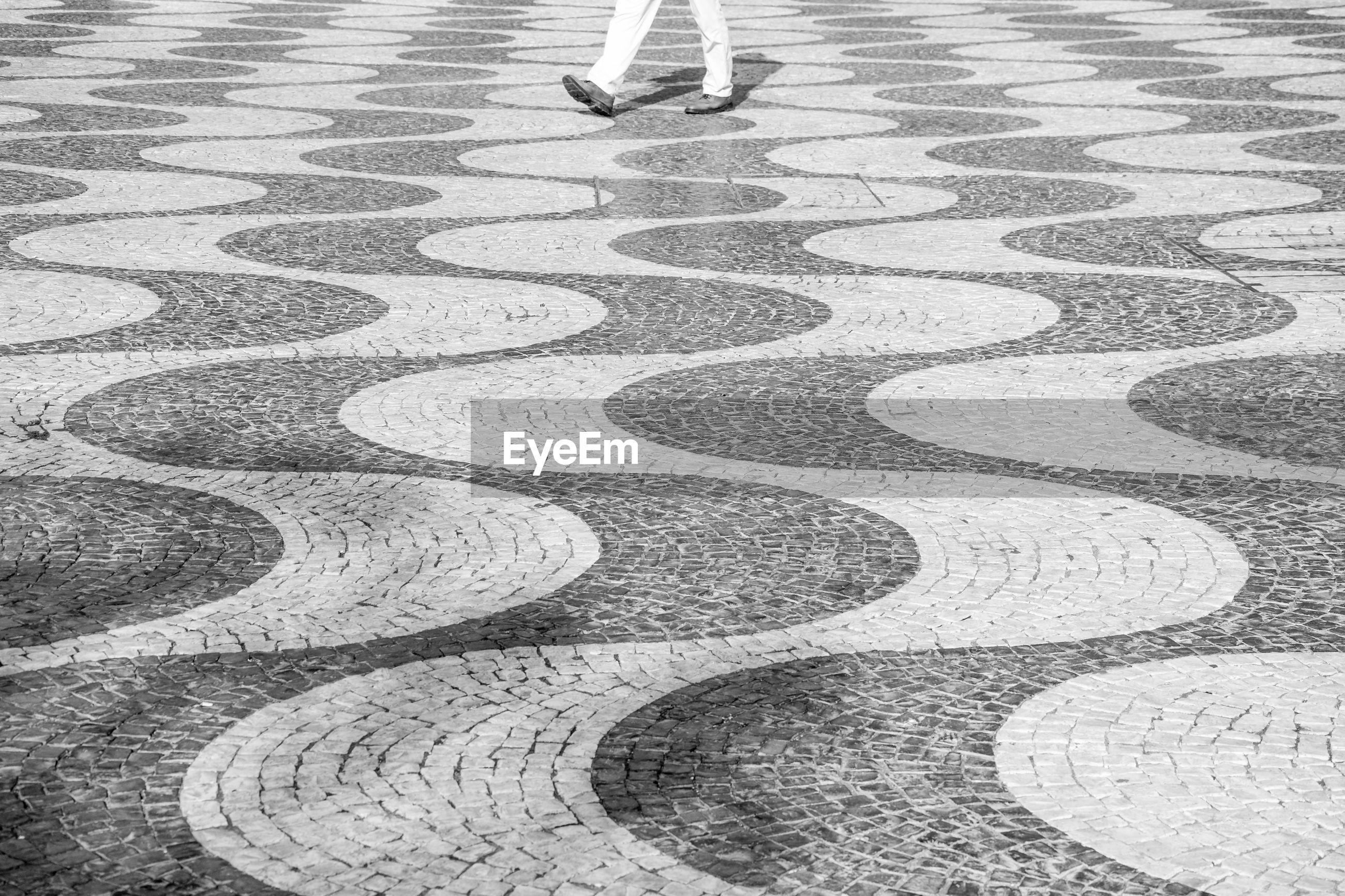 LOW SECTION OF MEN WALKING ON FOOTPATH
