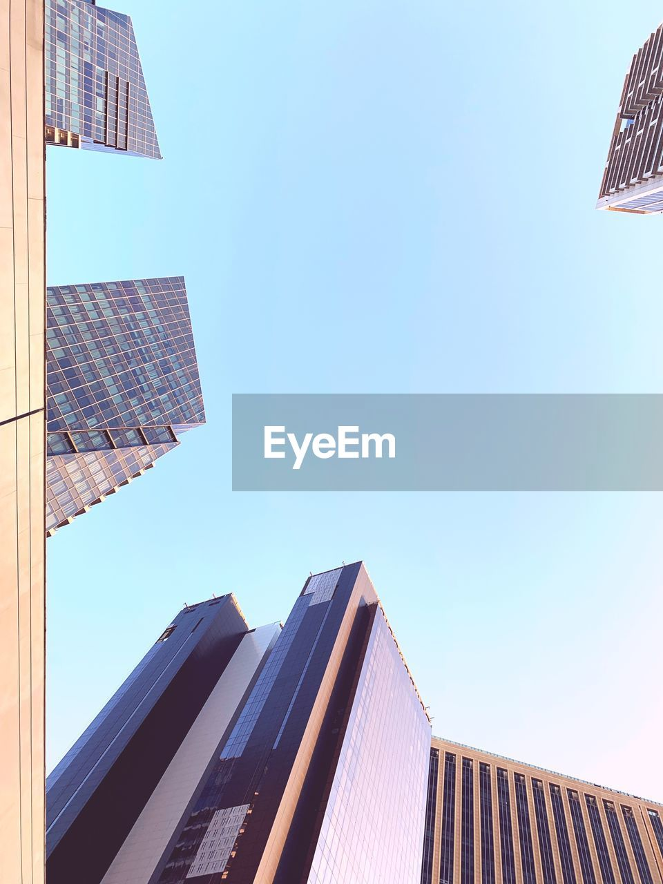 built structure, building exterior, architecture, building, sky, office building exterior, city, low angle view, clear sky, skyscraper, office, nature, modern, tall - high, day, blue, sunlight, no people, glass - material, outdoors, directly below, financial district