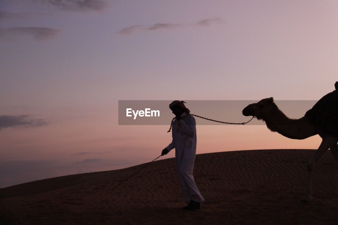 Man With Camel At Desert Against Sky During Sunset
