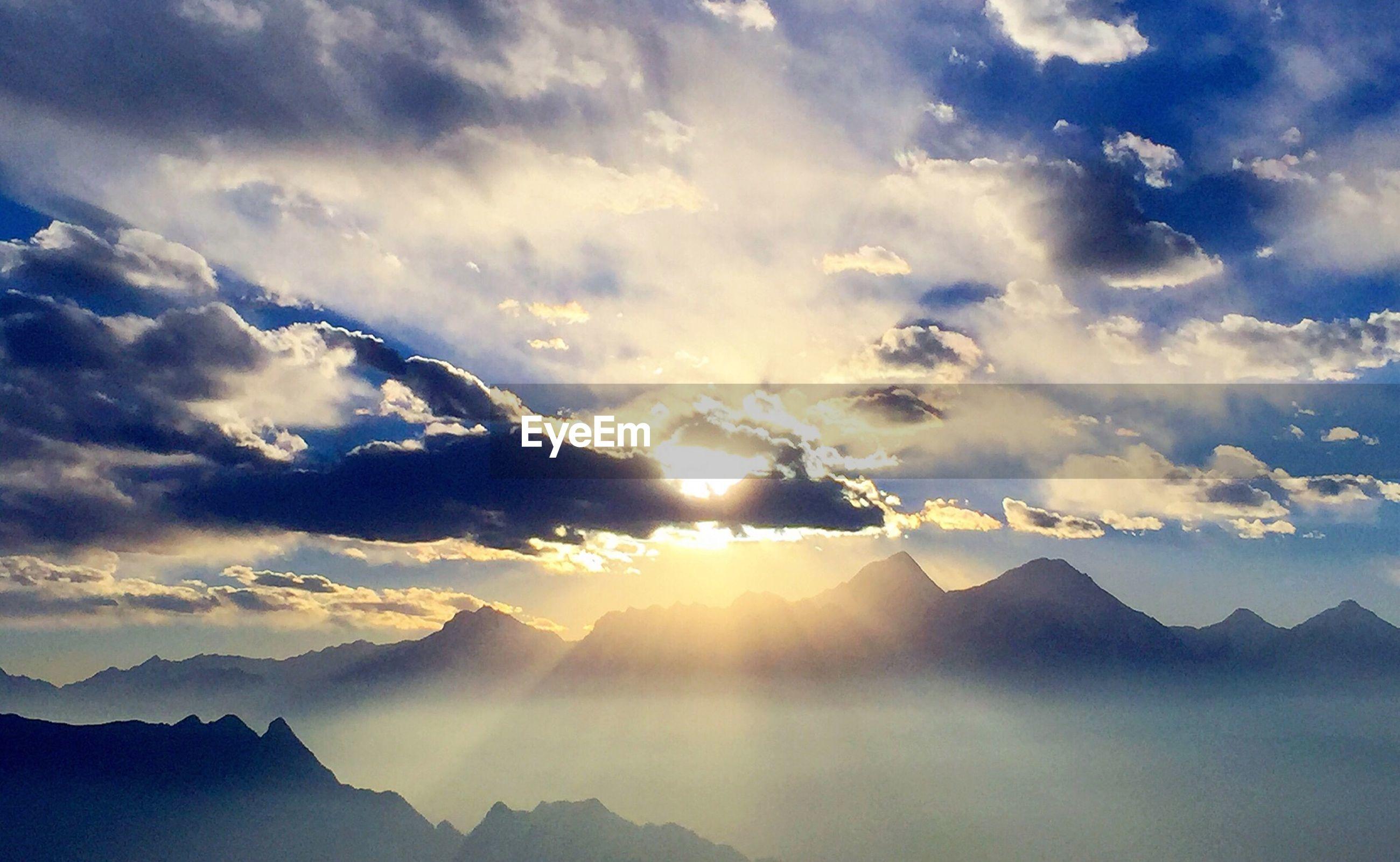 scenics, tranquil scene, mountain, beauty in nature, tranquility, sky, mountain range, cloud - sky, nature, sunset, sun, landscape, idyllic, sunbeam, cloud, sunlight, cloudy, majestic, silhouette, non-urban scene