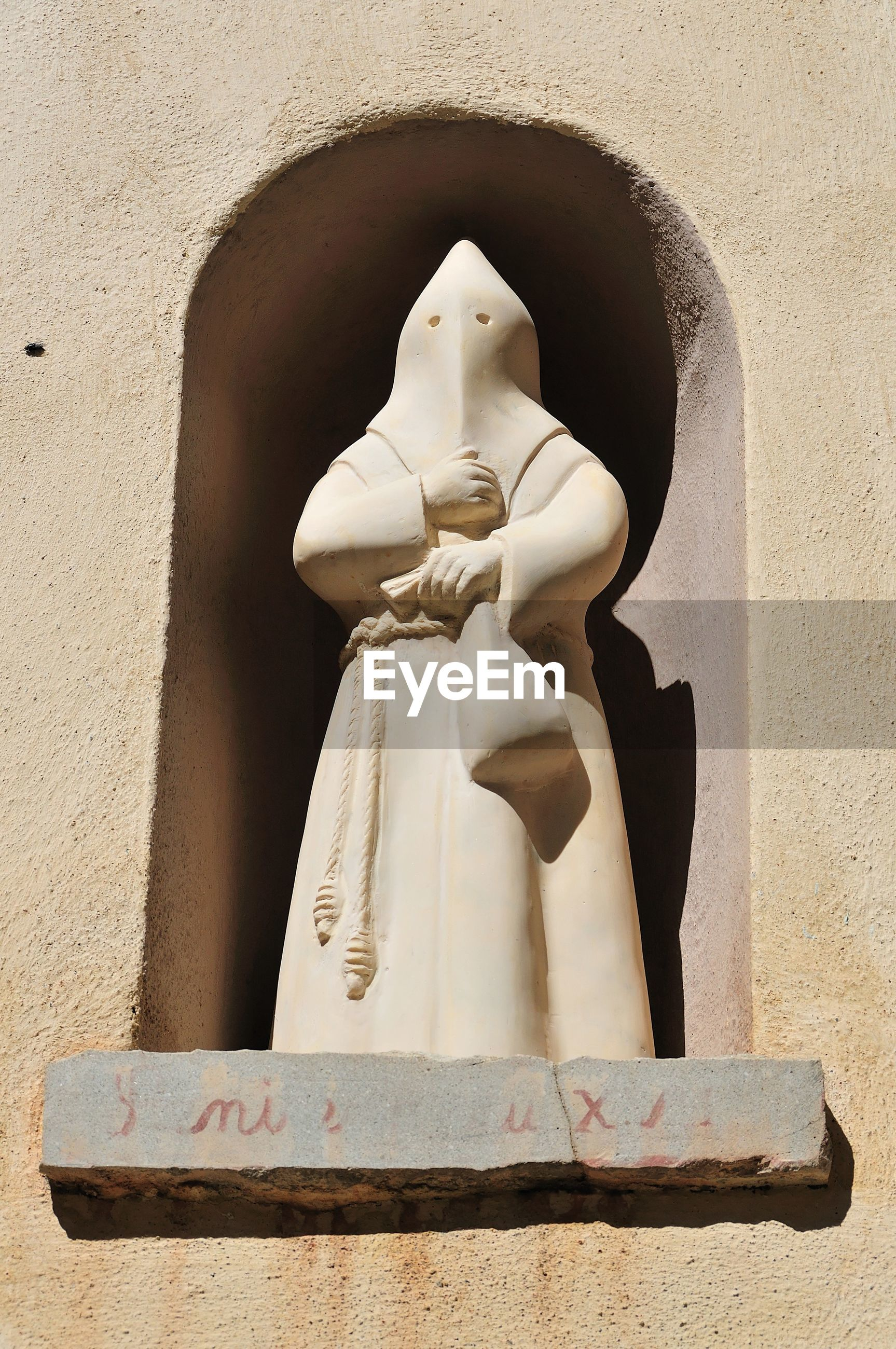 LOW ANGLE VIEW OF STATUE OF MAN AGAINST WALL