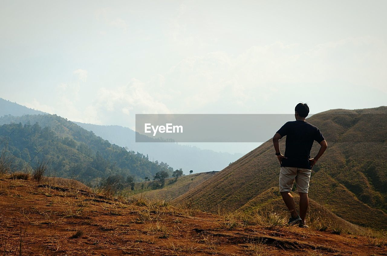 mountain, rear view, one person, beauty in nature, scenics - nature, real people, leisure activity, full length, tranquil scene, non-urban scene, landscape, tranquility, standing, sky, lifestyles, adventure, environment, men, idyllic, nature, mountain range, outdoors, looking at view