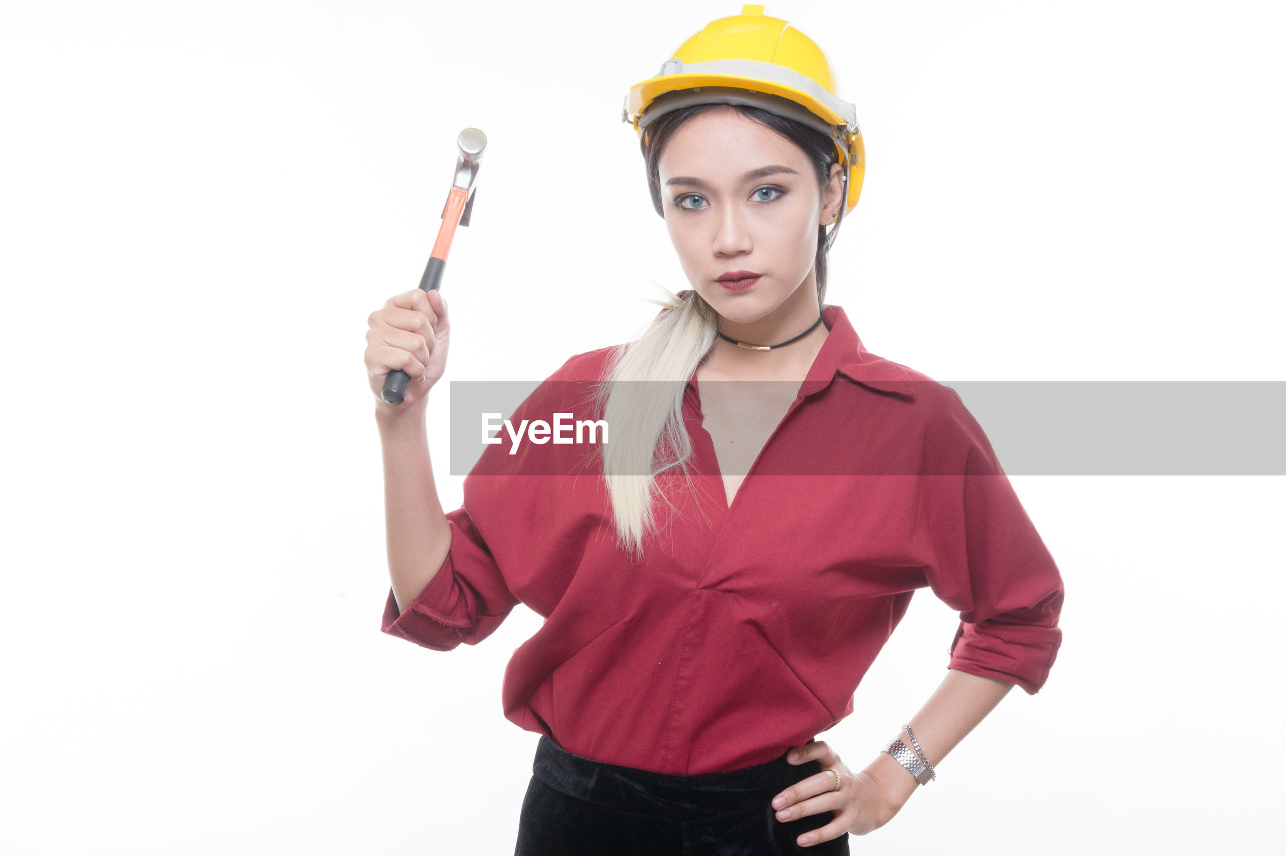 Confident young architect wearing yellow hardhat holding hammer while standing against white background