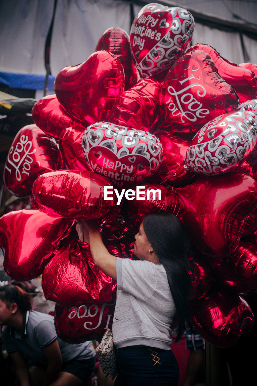 Side view of woman holding red heart shape balloons in city