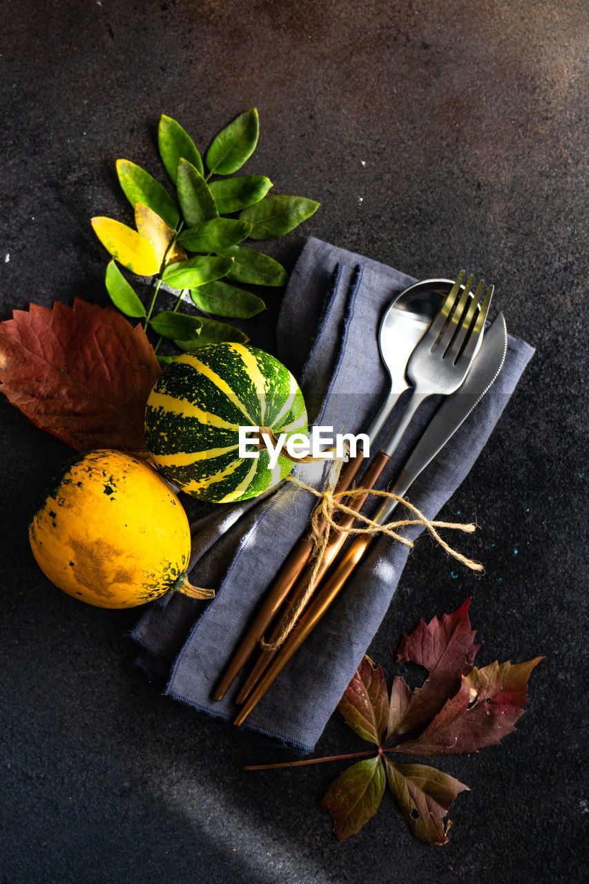 high angle view, freshness, no people, still life, food, table, food and drink, healthy eating, indoors, leaf, close-up, wellbeing, plant part, kitchen utensil, flower, directly above, yellow, fruit, eating utensil, fork, table knife, tray