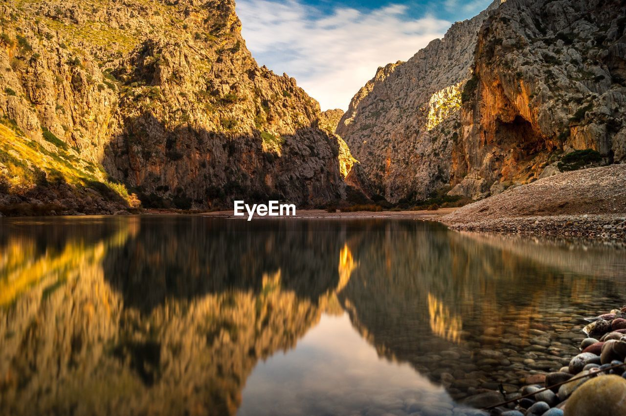 water, scenics - nature, beauty in nature, mountain, rock, tranquility, lake, reflection, tranquil scene, solid, rock - object, nature, mountain range, sky, non-urban scene, idyllic, waterfront, no people, day, outdoors, formation, eroded