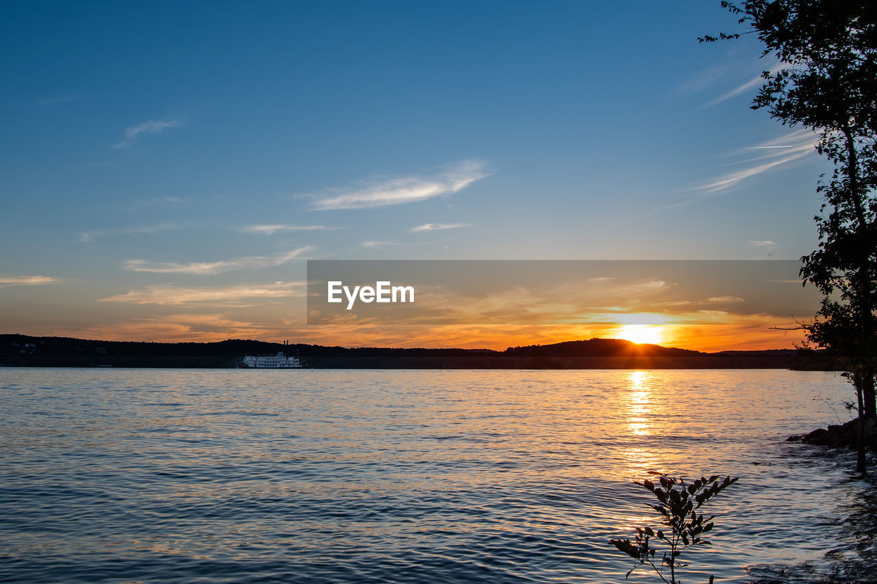 sky, sunset, water, beauty in nature, scenics - nature, tranquility, tranquil scene, cloud - sky, nature, silhouette, tree, reflection, idyllic, sunlight, no people, non-urban scene, orange color, lake, waterfront, sun, outdoors