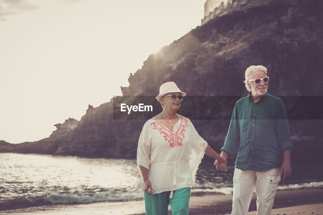 Senior Couple Holding Hands On Shore At Beach