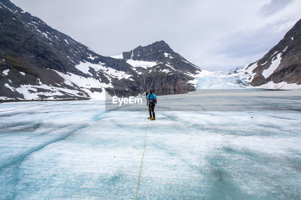 Hikers On Frozen Lake Amidst Mountains