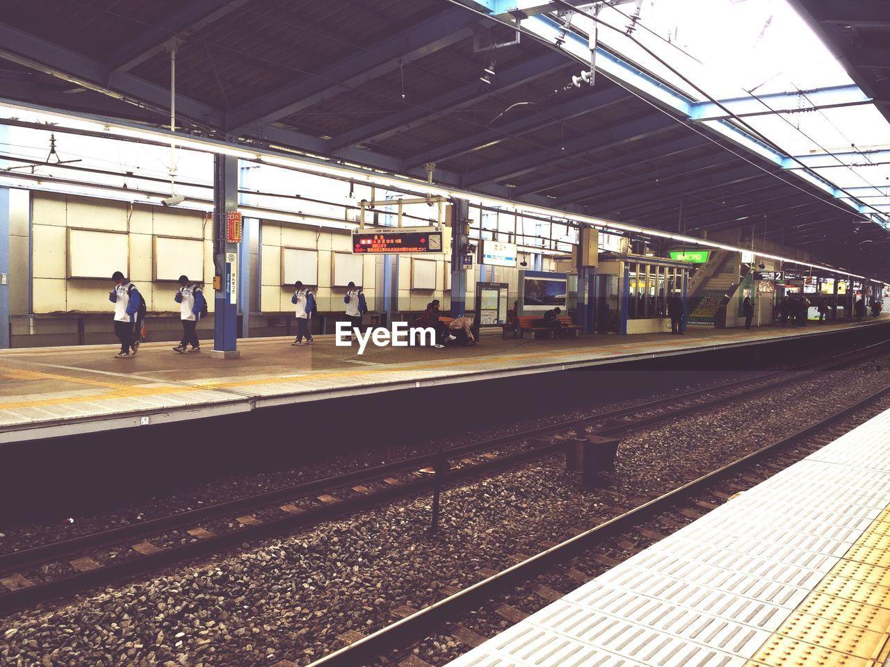 Multiple exposure of man walking on railroad platform