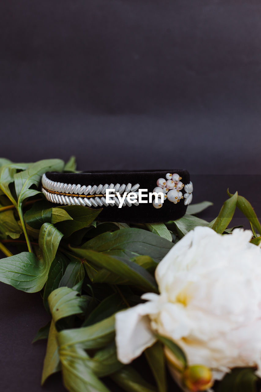 Close-up of white flowers and bracelet on table