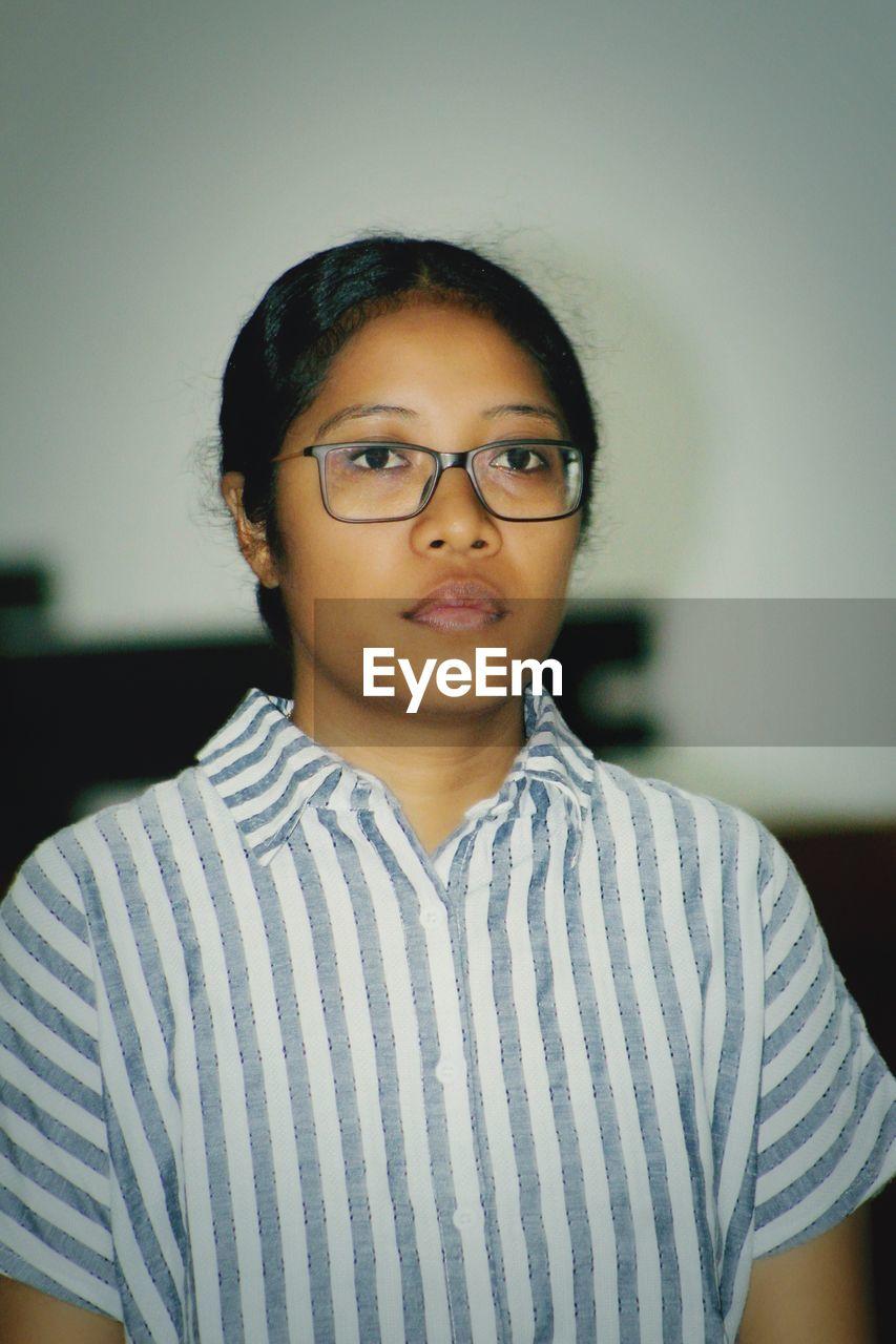 Woman wearing eyeglasses looking away at home