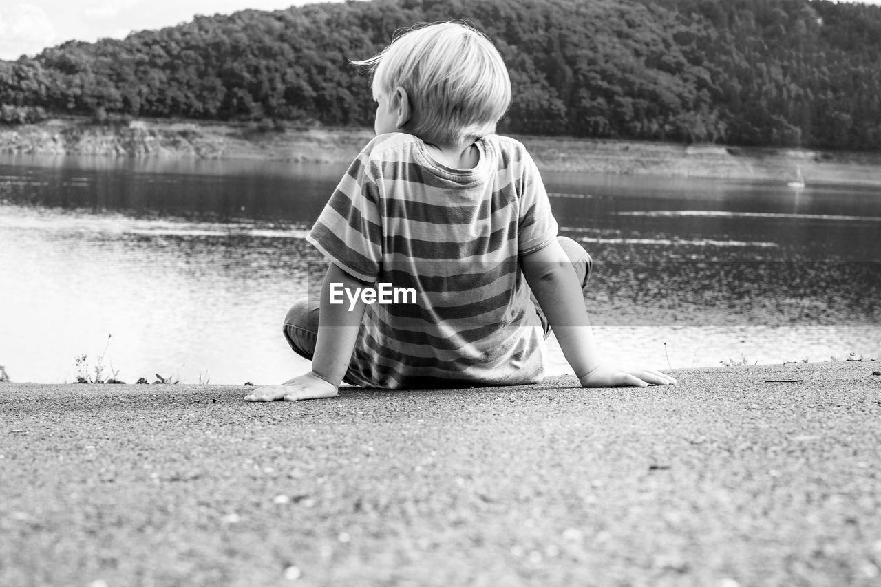 Rear view of boy sitting at lakeshore
