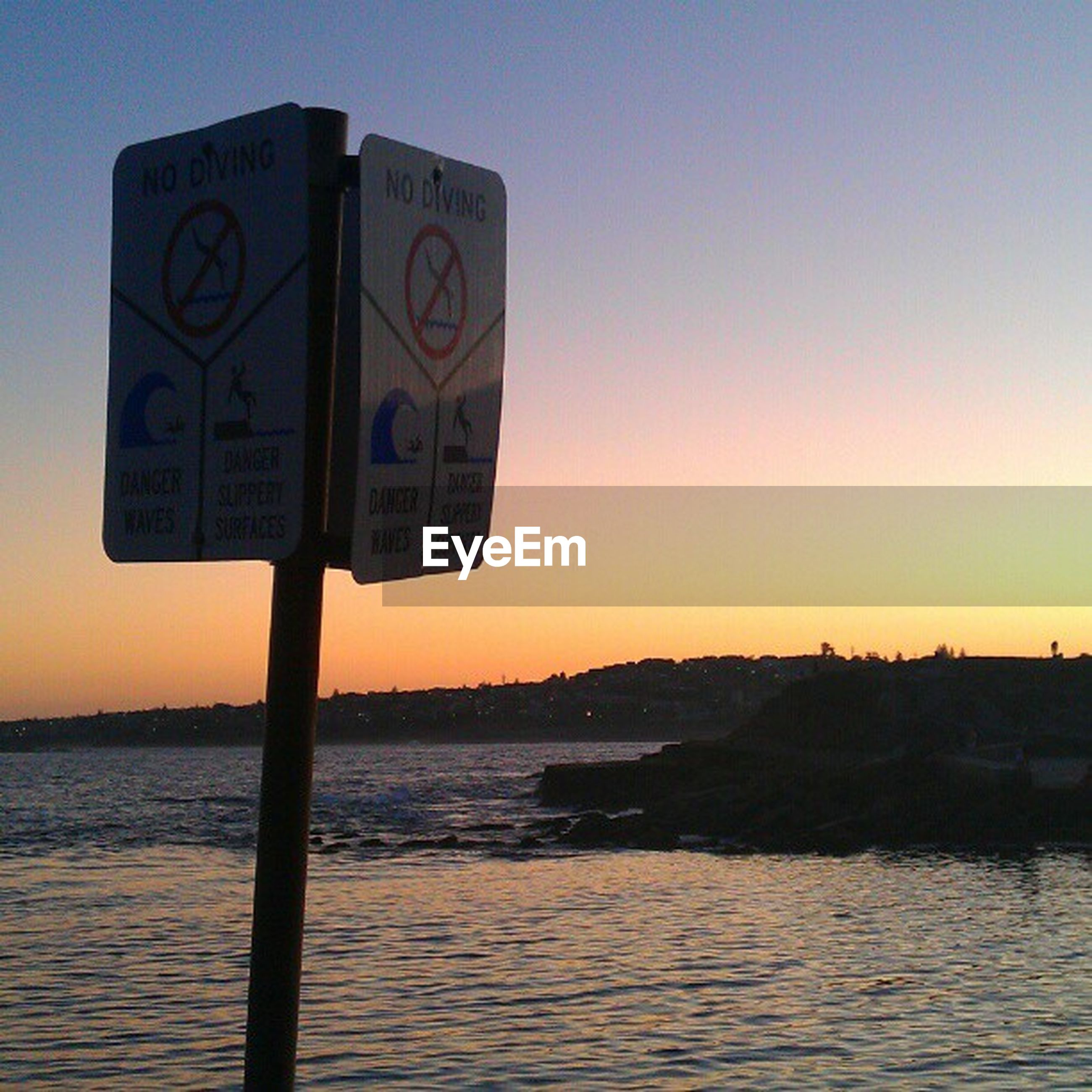 sunset, water, sea, communication, guidance, text, tranquility, tranquil scene, orange color, scenics, rippled, clear sky, sky, beauty in nature, western script, waterfront, nature, warning sign, direction, silhouette
